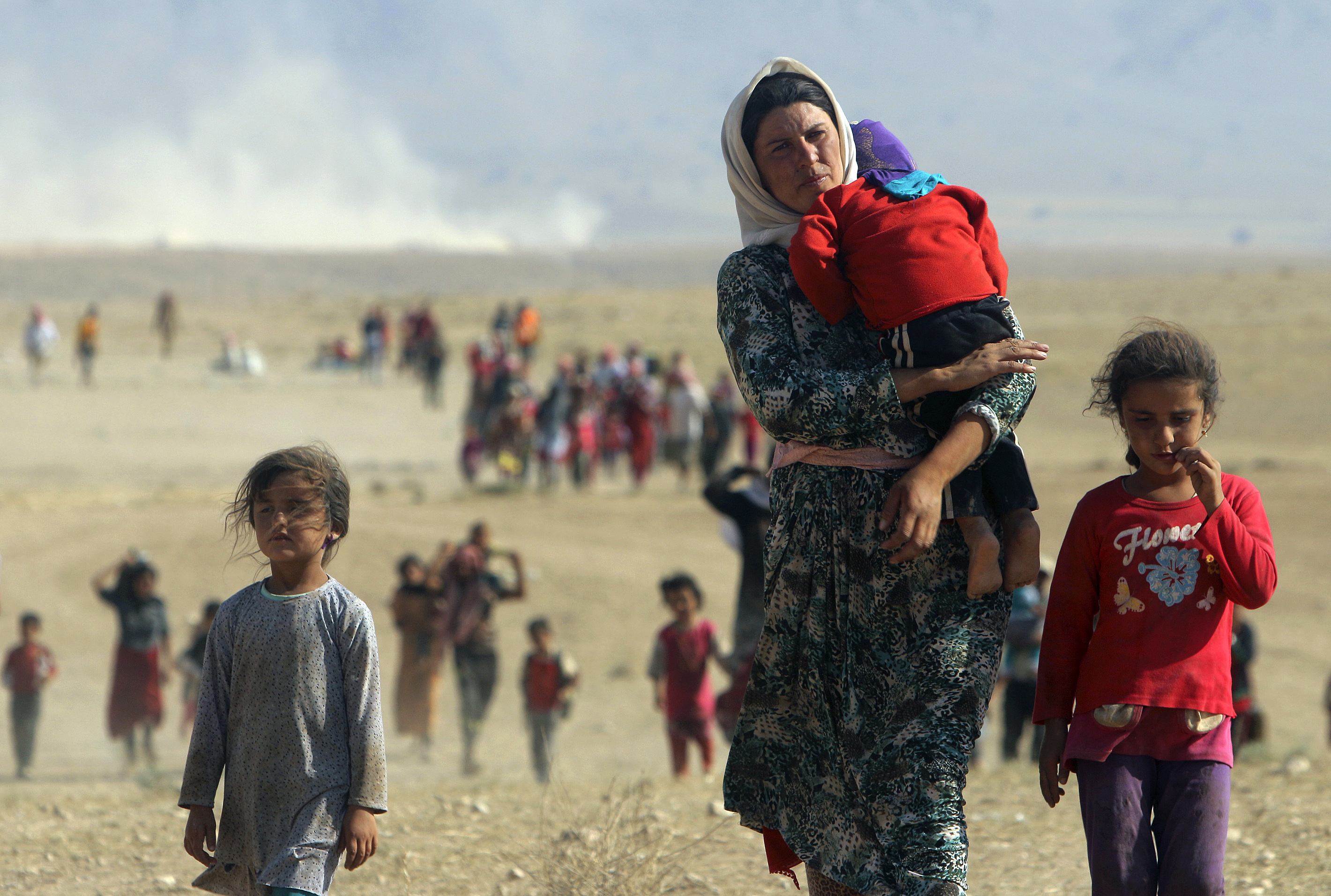 Displaced Yezidi people flee violence from forces loyal to ISIS, near the Syrian border town of Elierbeh, on Aug. 11, 2014
