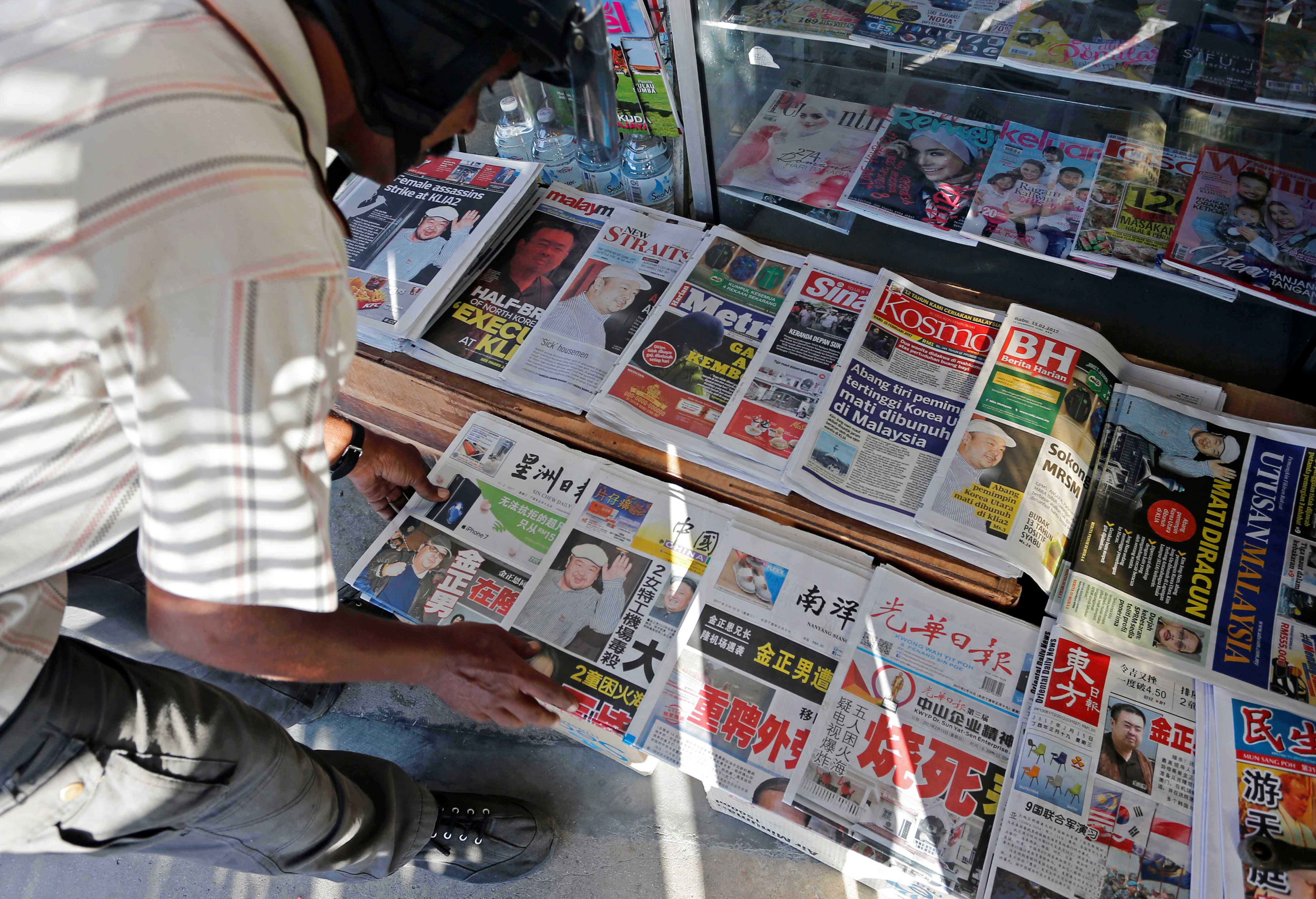 A newspaper vendor arranges newspapers showing front pages reporting the death of Kim Jong Nam, at a newsstand outside Kuala Lumpur on Feb. 15, 2017