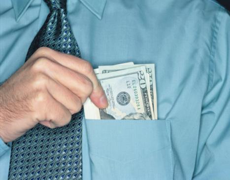 Man holding $20 bills in shirt pocket