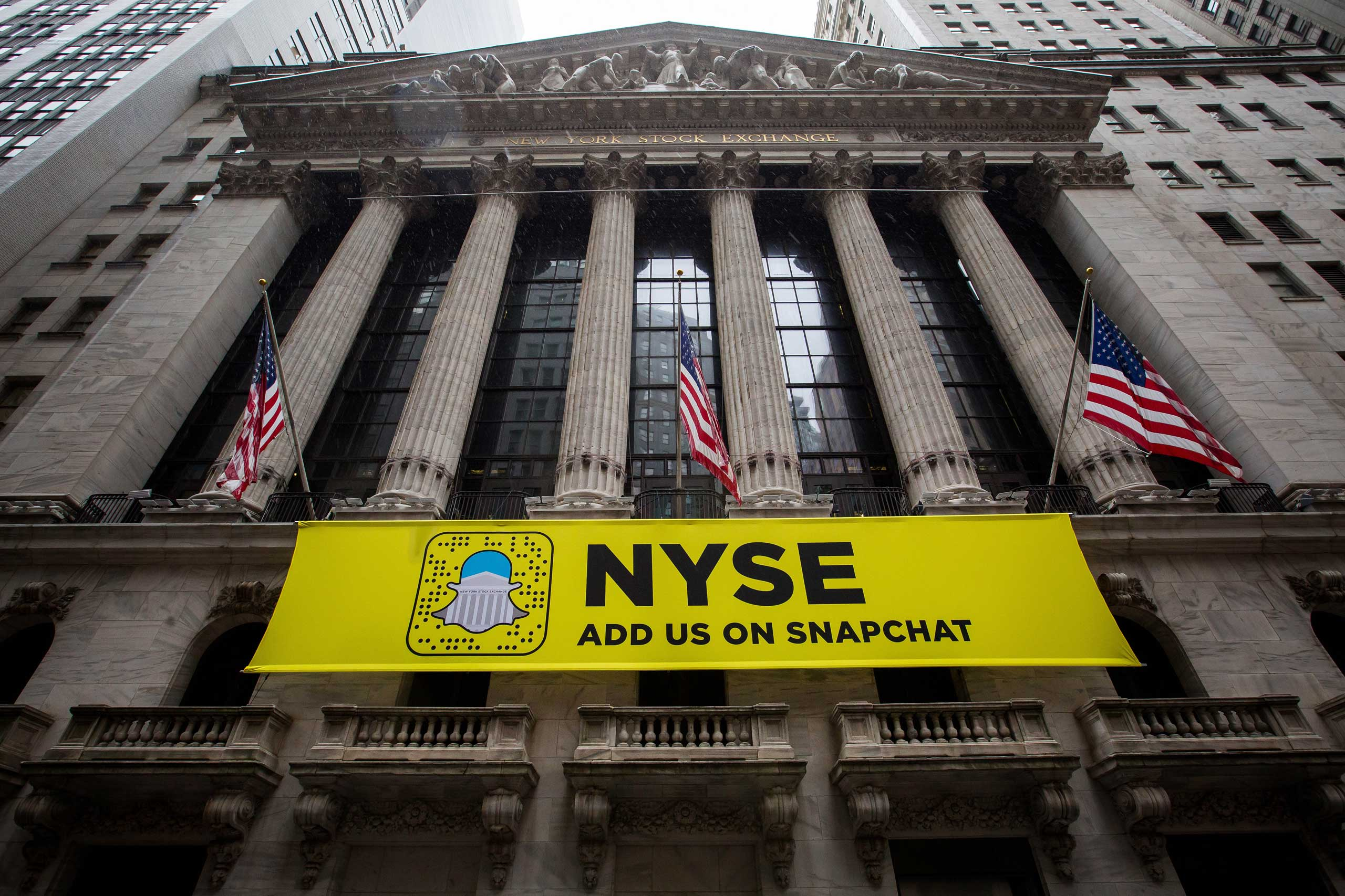 American flags fly above a Snapchat sign displayed outside of the New York Stock Exchange (NYSE) stands in New York, on Oct. 21, 2016.