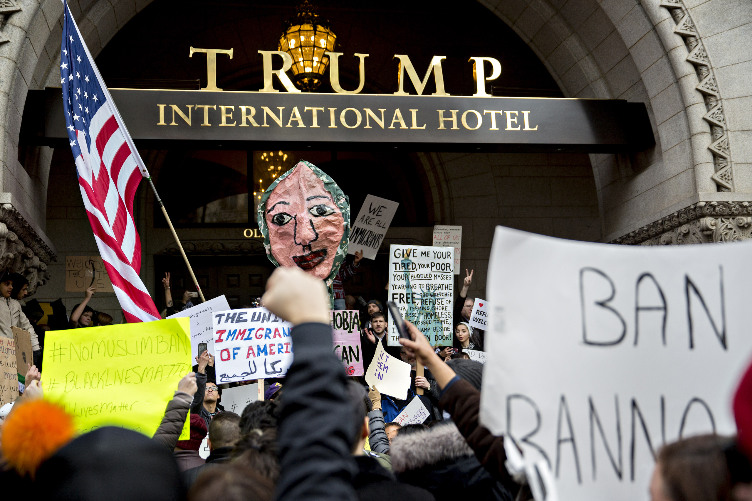 Demonstrators hold up a signs outside the Trump International Hotel during a protest against U.S. President Donald Trump's executive order blocking visitors from seven predominantly Muslim nations in Washington, D.C., on Jan. 29, 2017.