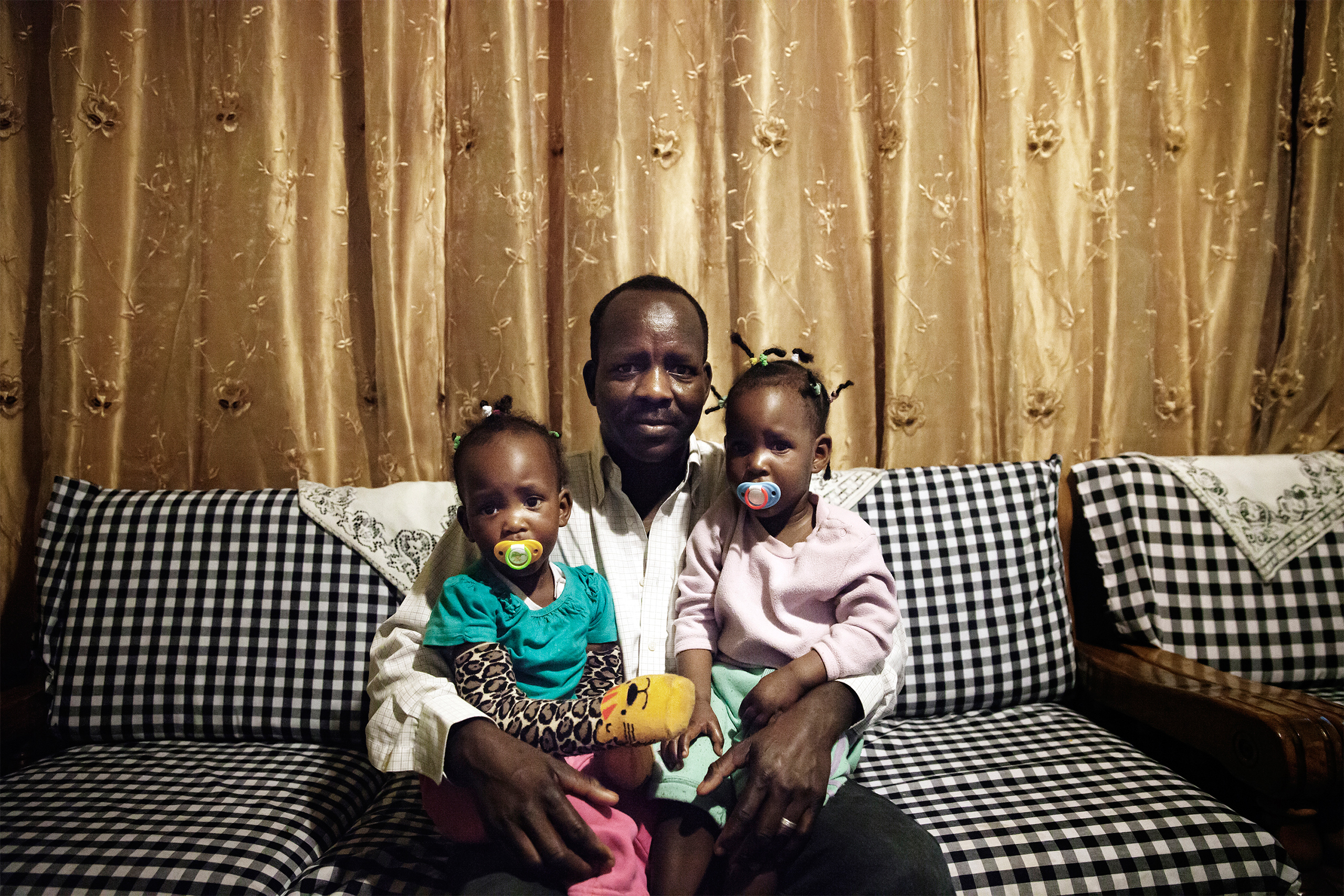 "Boshora Adam, an African refugee, appears with his twin daughters in their home in Tel Aviv, Israel.  ""The hardest part about raising my children in Israel is that it's becoming more segregated,  he says.  On the playground you notice that parents keep their children away from African children, and this worries me for my children's future."""