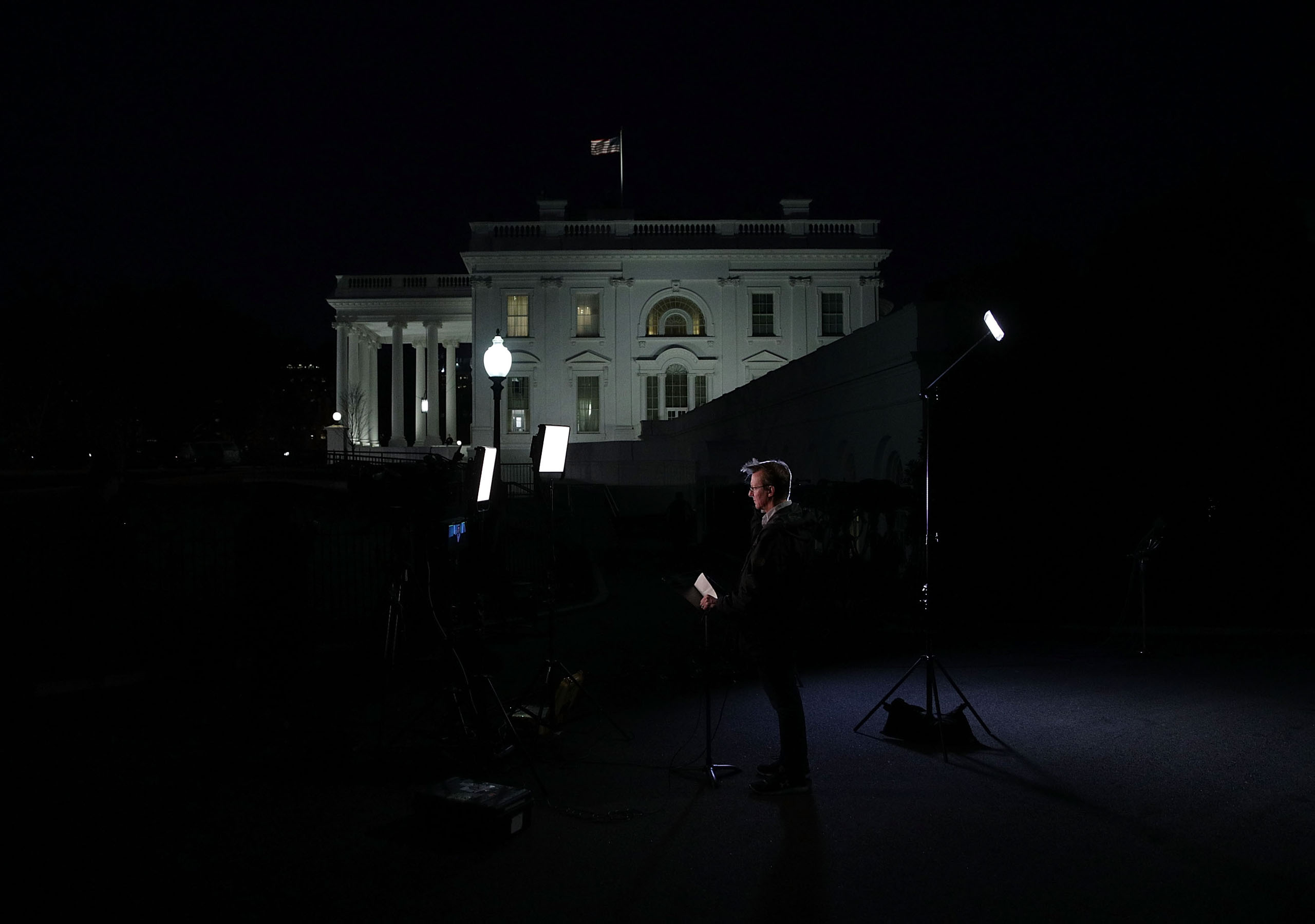 A TV news crew sets up a stand on the ground of the White House on Feb. 7, 2017.