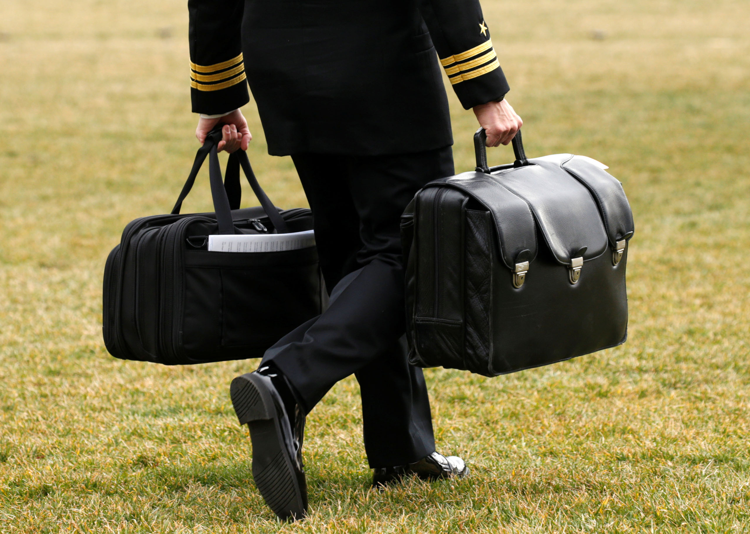A military aide, carrying the  football  containing launch codes for nuclear weapons, accompanies President Donald Trump onto Marine One upon Trump's departure from the White House in Washington, on Feb. 3, 2017.