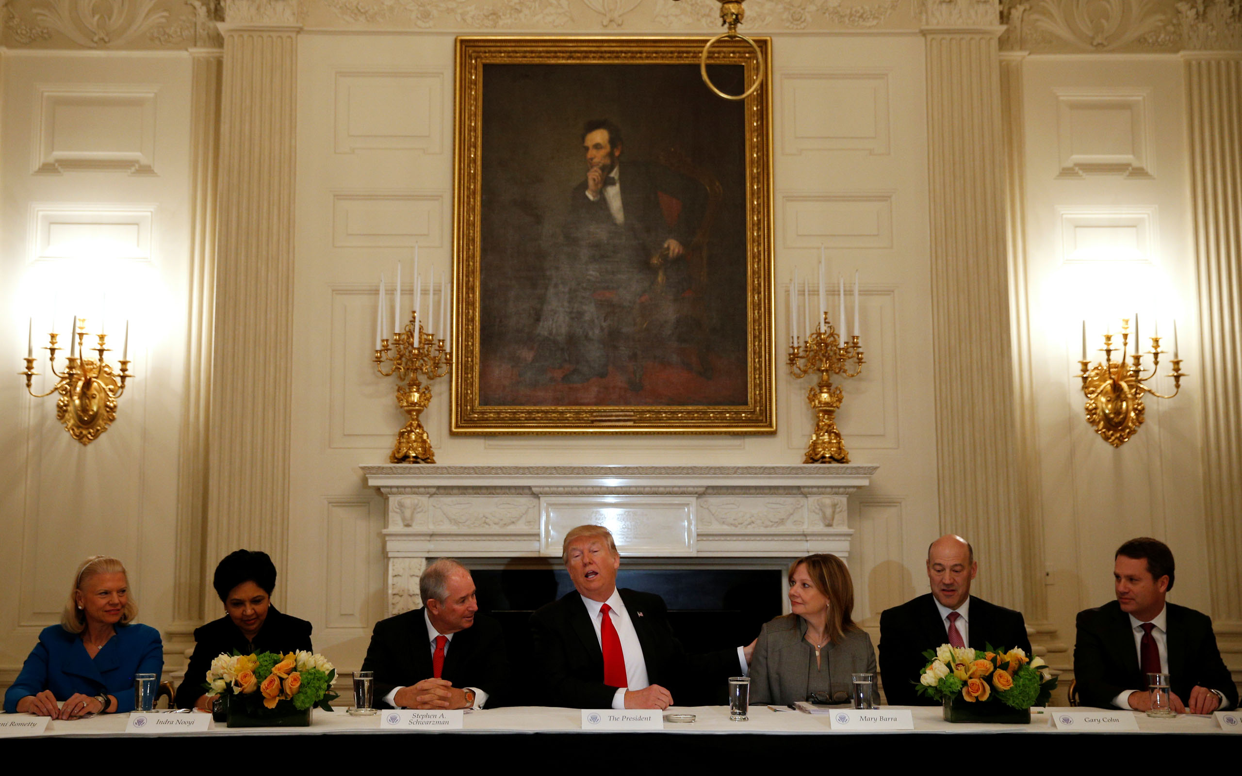 President Donald Trump puts his hand on General Motors CEO Mary Barra while hosting a strategy and policy forum with chief executives of major U.S. companies at the White House in Washington, on Feb. 3, 2017.