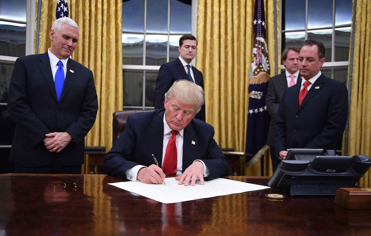 President Donald Trump signs an executive order as Vice President Mike Pence and Chief of Staff Reince Priebus look on at the White House in Washington, D.C. on Jan. 20, 2017.