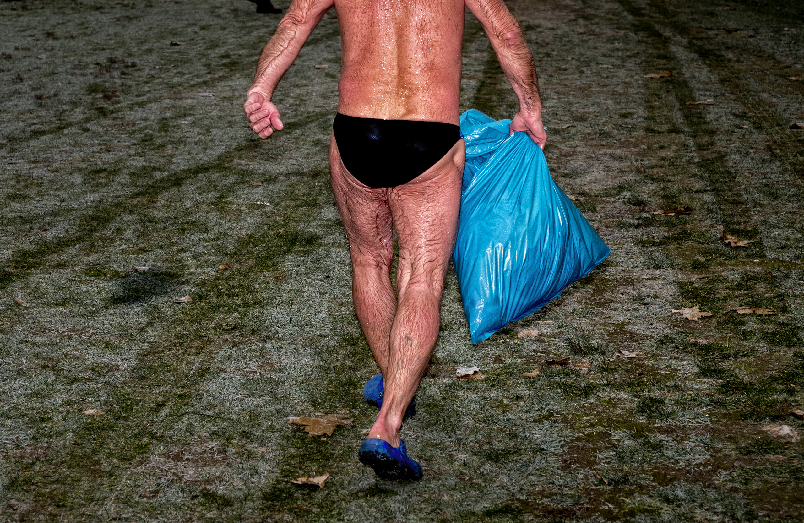 A swimmer holds a plastic bag containing clothes in his hand after completing a race in the Labe River on Dec. 17 2016.