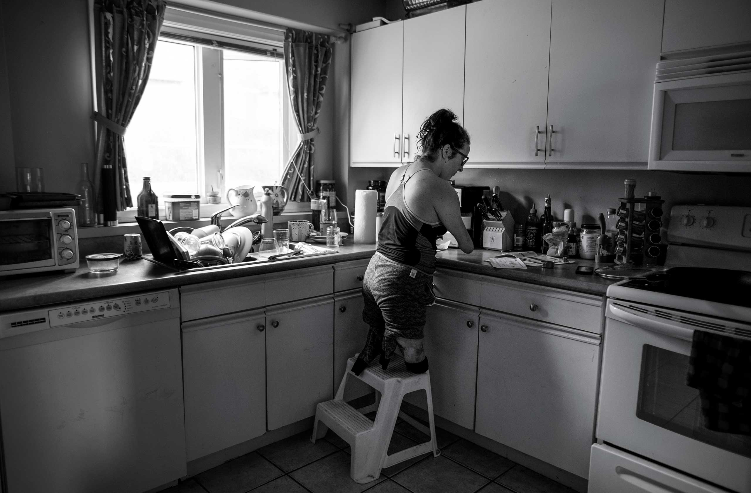 Lindsay stands on a step stool while making coffee early in the morning in her home in Halifax, Nova Scotia, Canada on Sept. 18, 2016.
