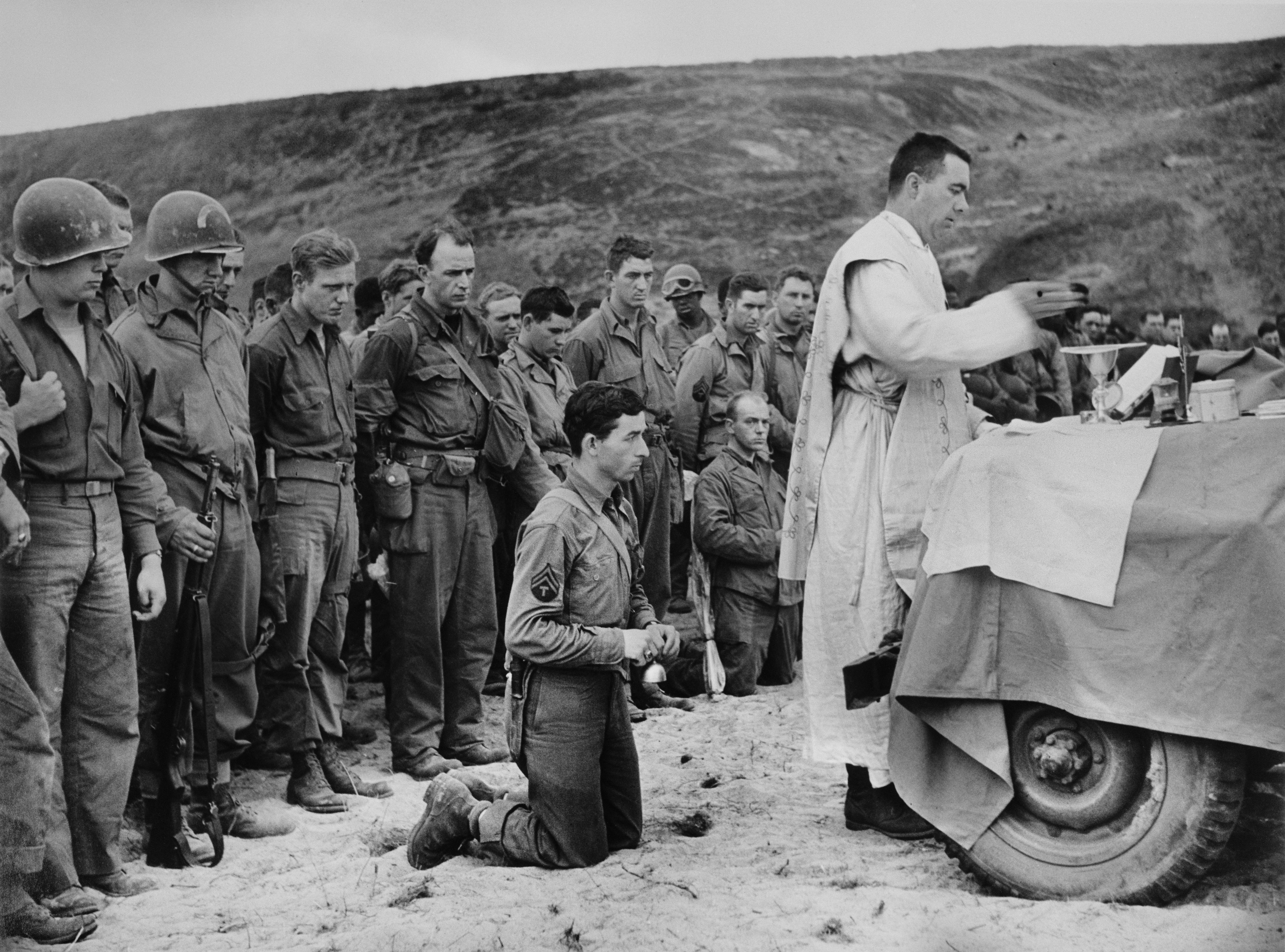 [Using the hood of a jeep as an altar, a Roman Catholic chaplain saying mass at the inauguration of an American cemetery, Omaha Beach, Normandy], June 1944