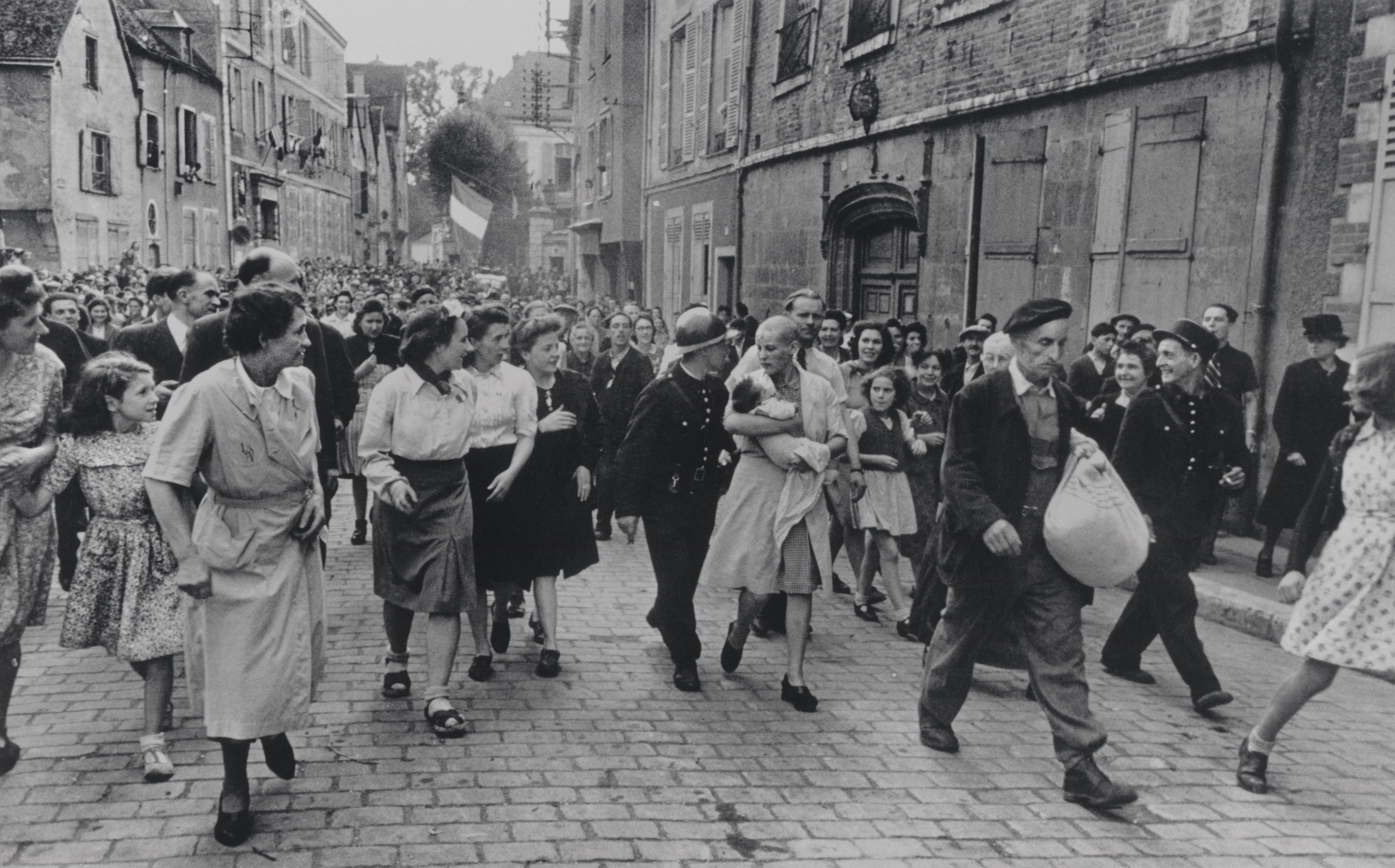 [French woman, who had a baby fathered by a Germany soldier, being marched through the streets after being punished by having her head shaved, Chartres, France], August 18, 1944