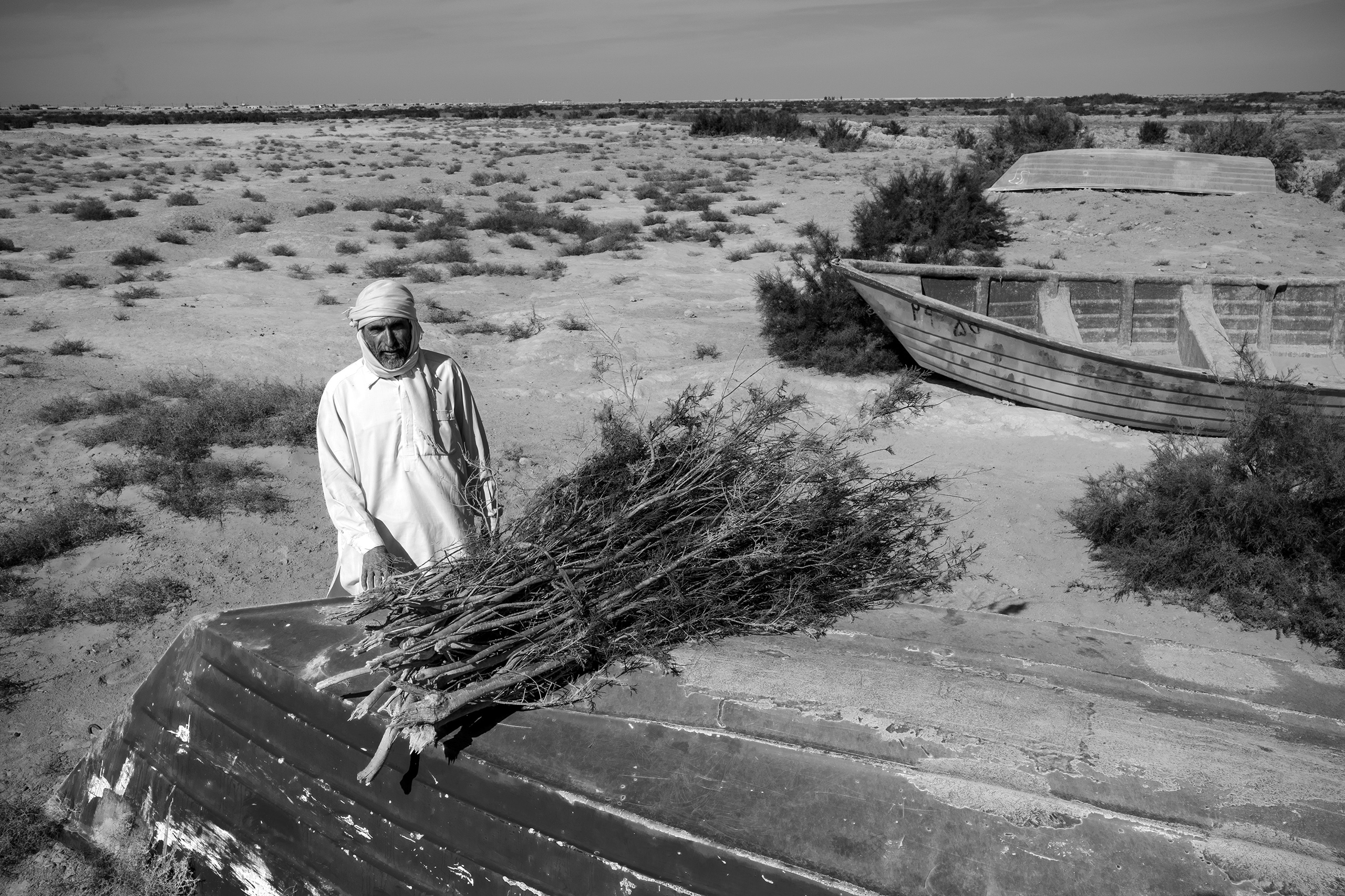 A fisherman sells tamarisk reeds in the dried-out seabed of Lake Hamoon.  At the border between Iran and Afghanistan, the Sistan Basin is one of the most arid places in the world. Drought and mismanagement of irrigation has contributed to drying out the lake, impacting wildlife and the livelihood of the local population, December 2016.