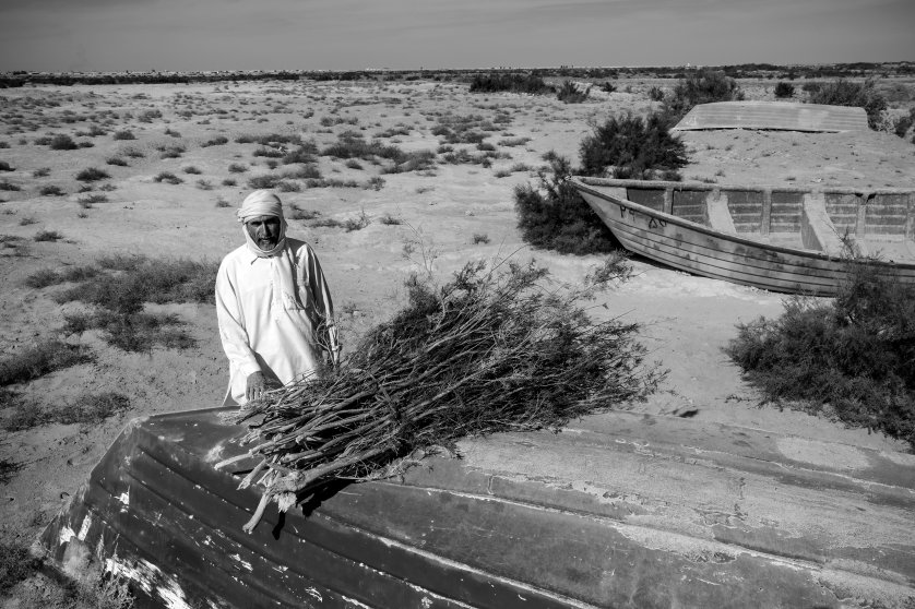 A fisherman sells tamarisk reeds in the dried-out seabed of Lake Hamoon.  At the border between Iran and Afghanistan, the Sistan Basin is one of the most arid places in the world. Drought and mismanagement of irrigation contributed to drying out the lake, thereby impacting wildlife and the livelihood of the local population, December 2016.