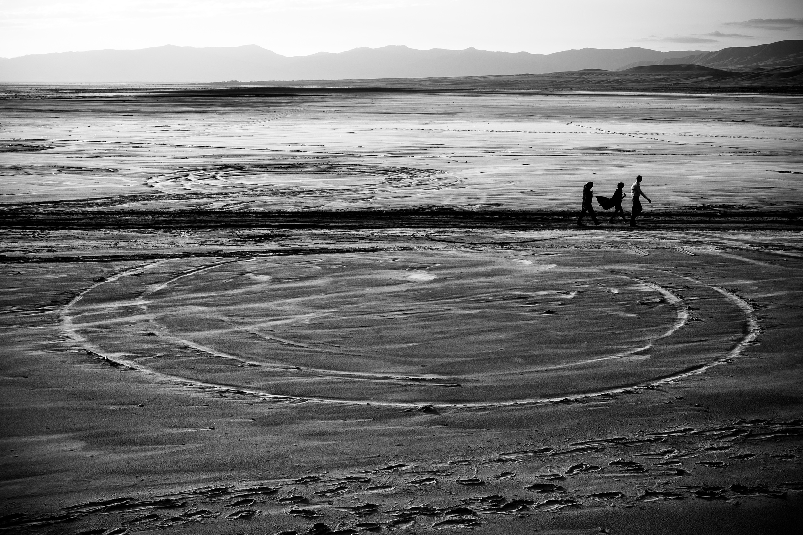 People walk on the dried Lake Urmia in northwestern Iran, near the Turkish border, which was  one of the largest saltwater lakes in the Middle East. The lake has been shrinking  over the last 20 years. This past summer algae and bacteria turned the water red, July 2016.