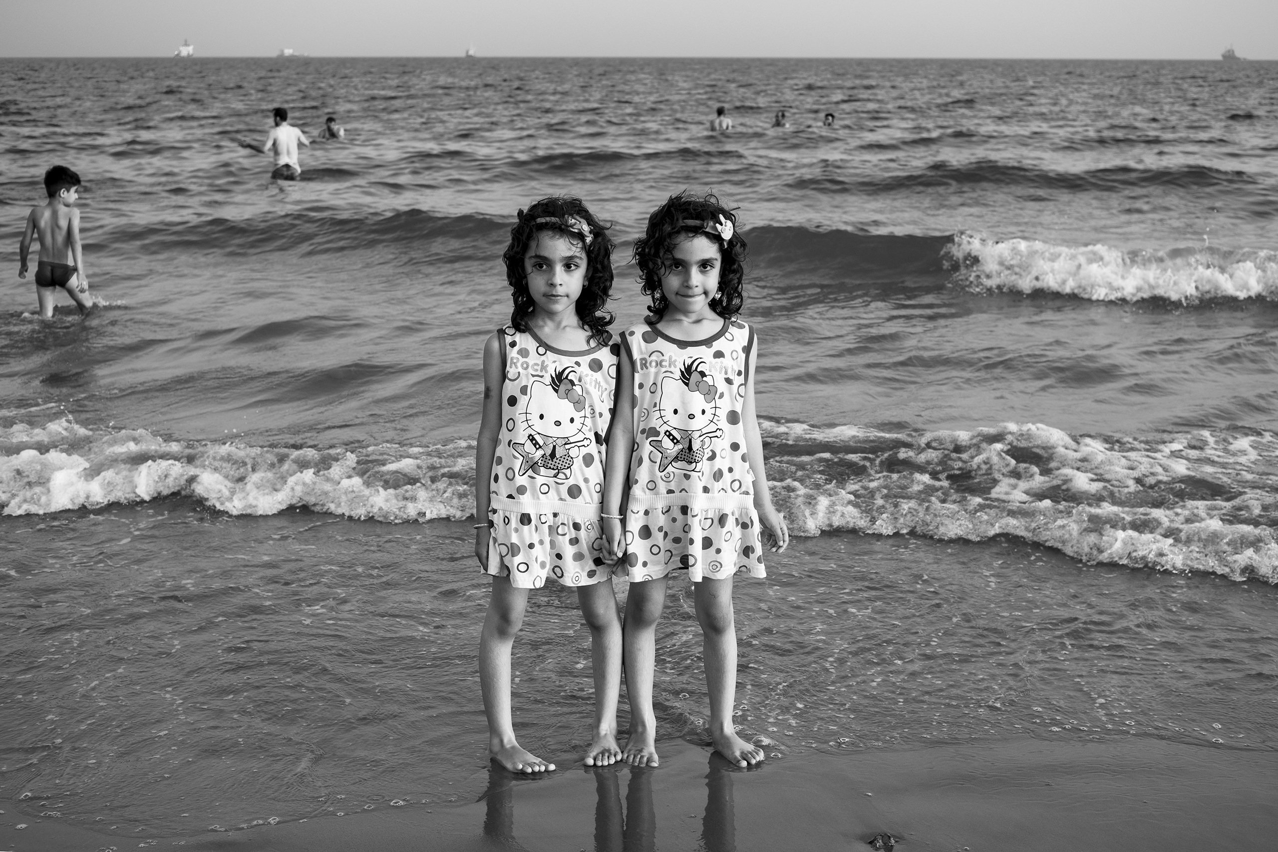 Twins escape from high temperatures at the seaside of Dayyer, Iran.  According to scientists, by 2070, if worldwide emissions aren't sufficiently reduced, the Persian Gulf will experience heat waves that will be impossible for many humans to survive, May 2016.