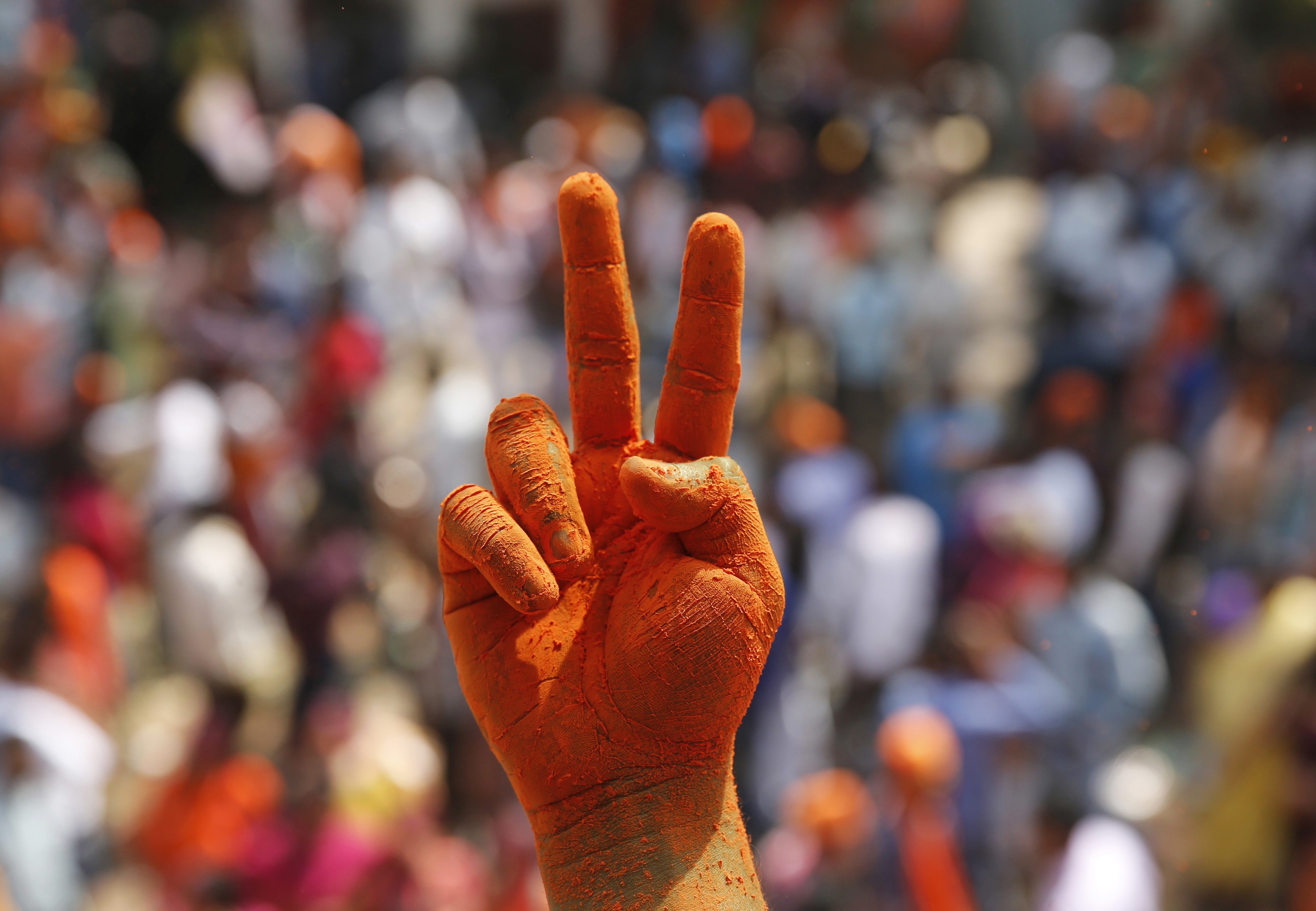 A Bharatiya Janata Party supporter's hands are covered in saffron color as he displays a victory sign in Lucknow, India, on March 11, 2017