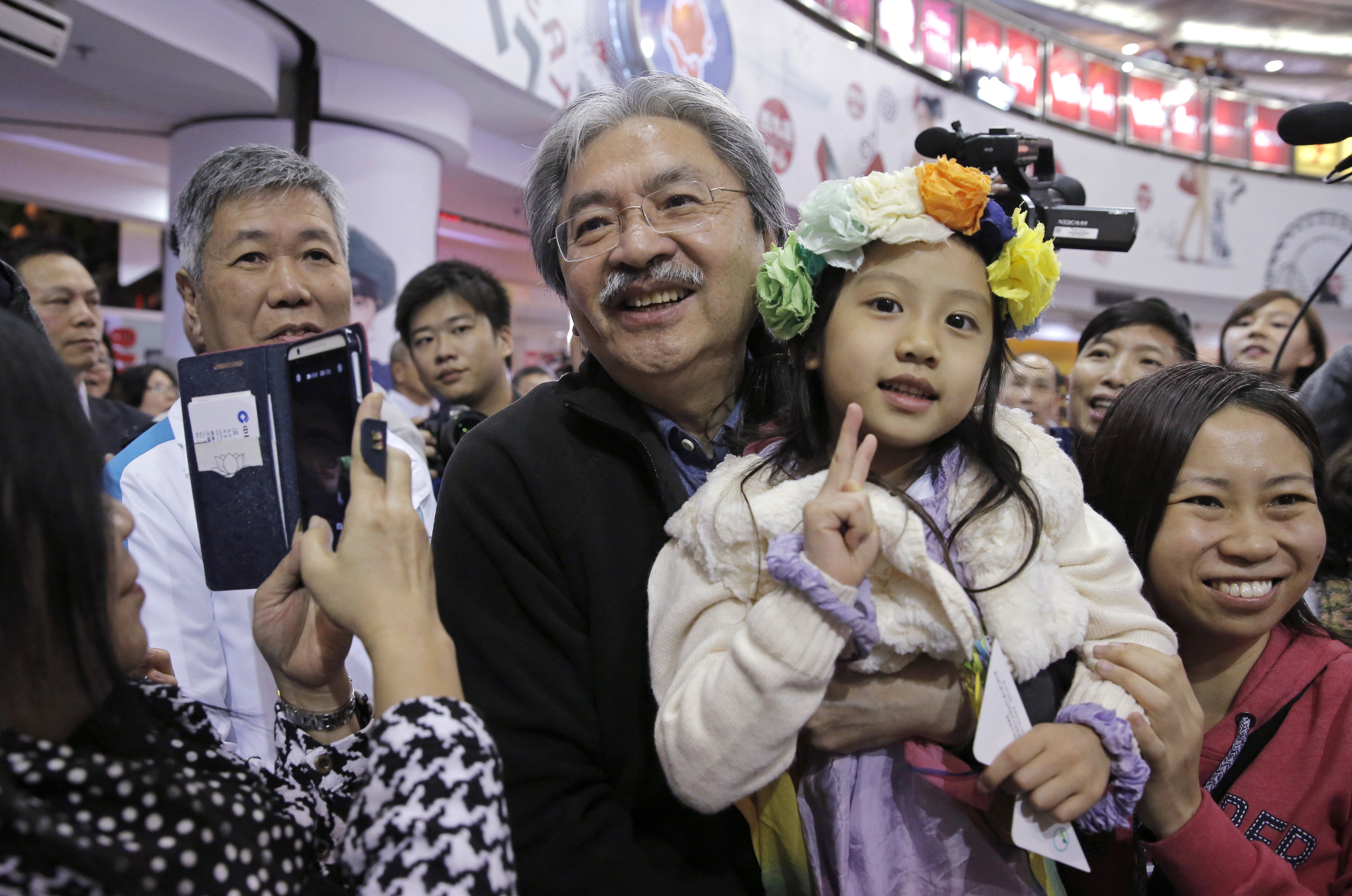 Chief Executive candidate, Hong Kong's former Financial Secretary John Tsang, center, holds a child as he poses for a photograph with his supporters at an election campaign in Hong Kong on March 16, 2017