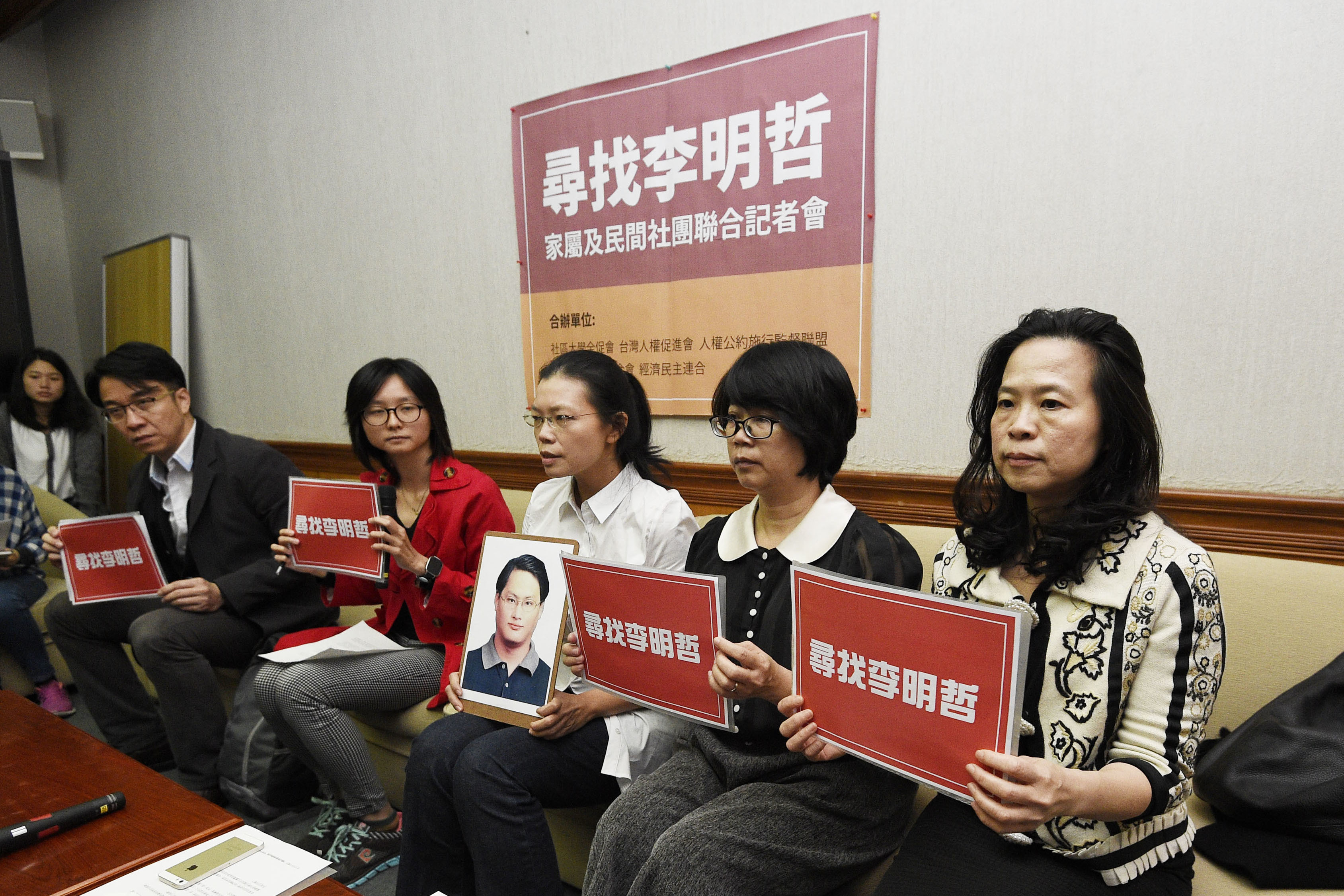 In this photo taken  March 24, 2017, Lee Ching-yu, third from right, holds up a photo of her missing husband, Taiwanese pro-democracy activist Lee Ming-che