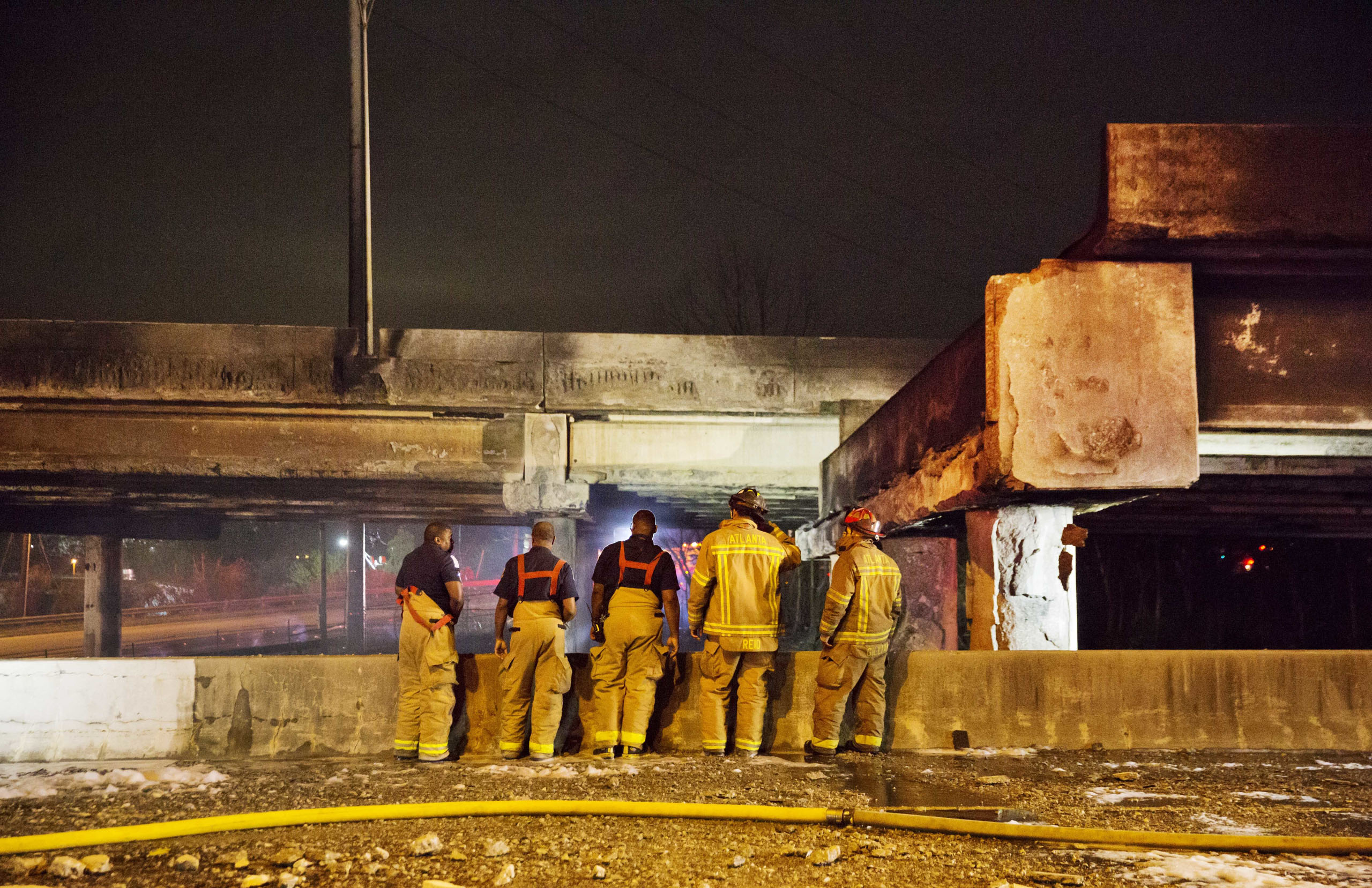 Firefighters survey the section of an overpass that collapsed from a large fire on Interstate 85 in Atlanta, Thursday, March 30, 2017.