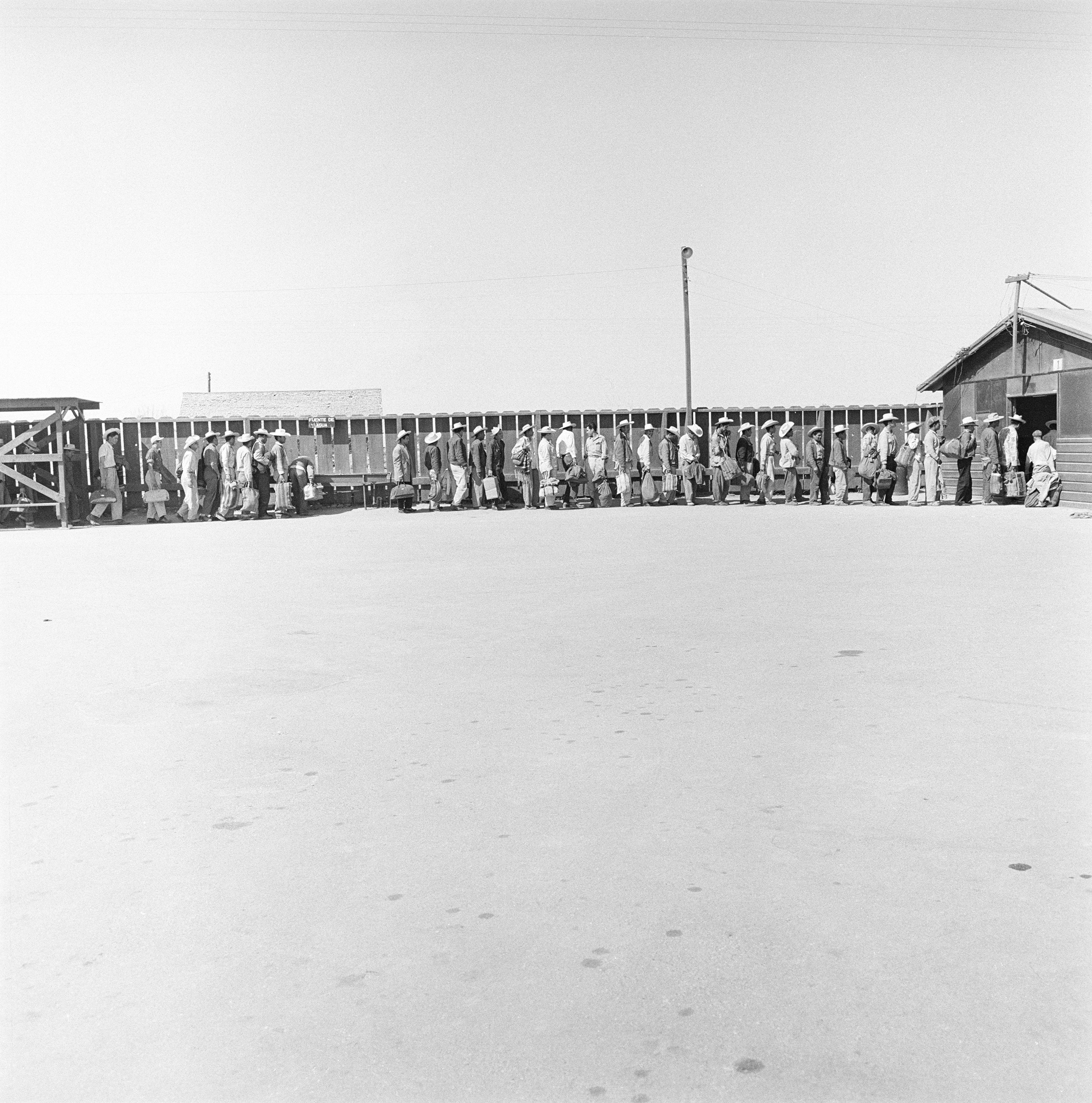 Mexican laborers in line at a reception depot for processing and assignment in El Centro, Calif., 1957.