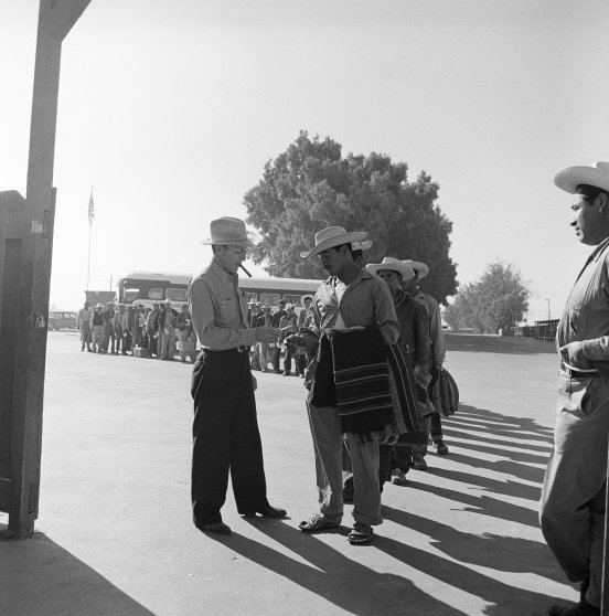 Mexican laborers show their permission to work papers as they arrive at a recruiting center in California, 1957.