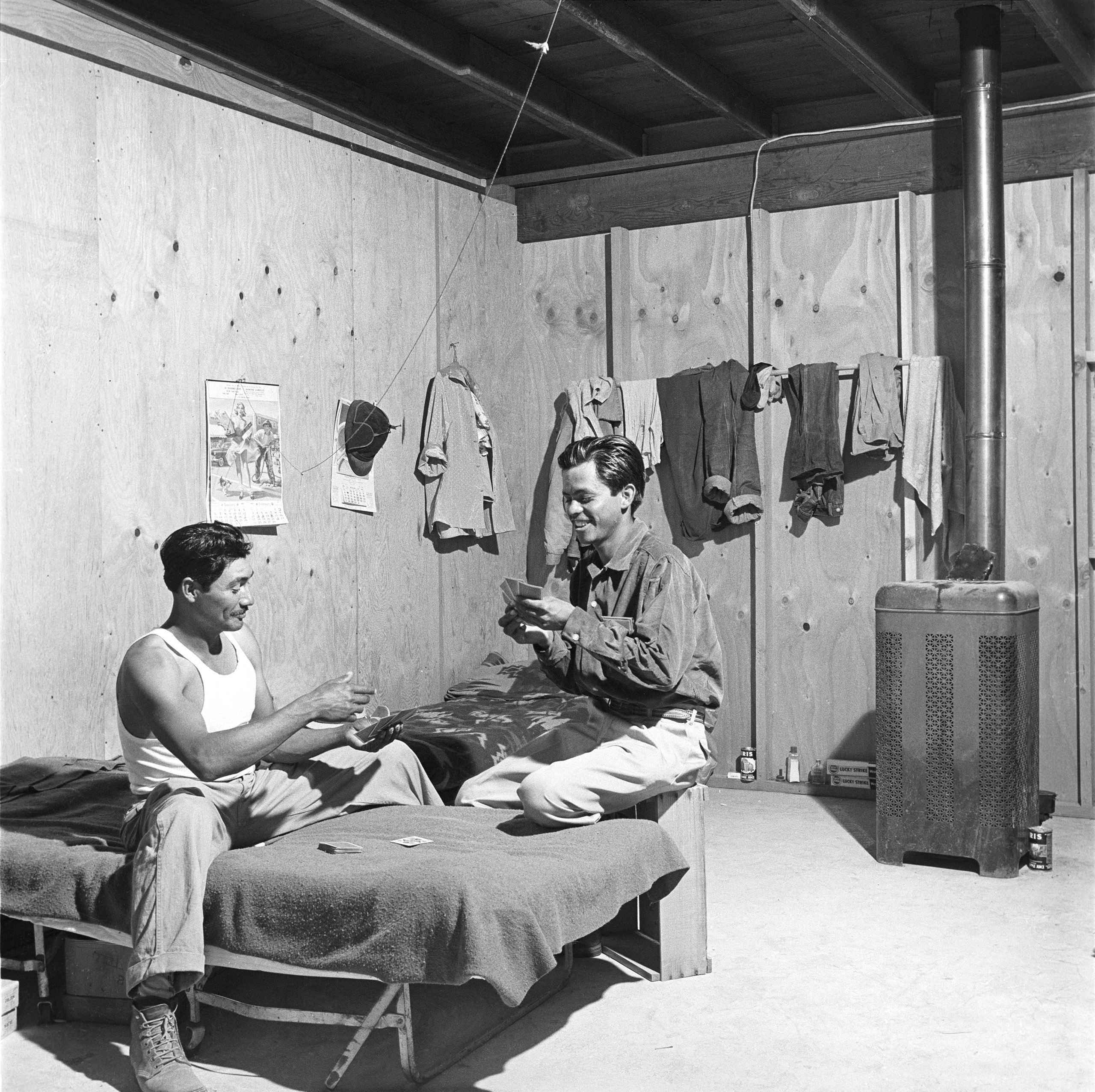 Tamayo relaxes with a fellow worker inside the temporary living quarters, California, 1957.