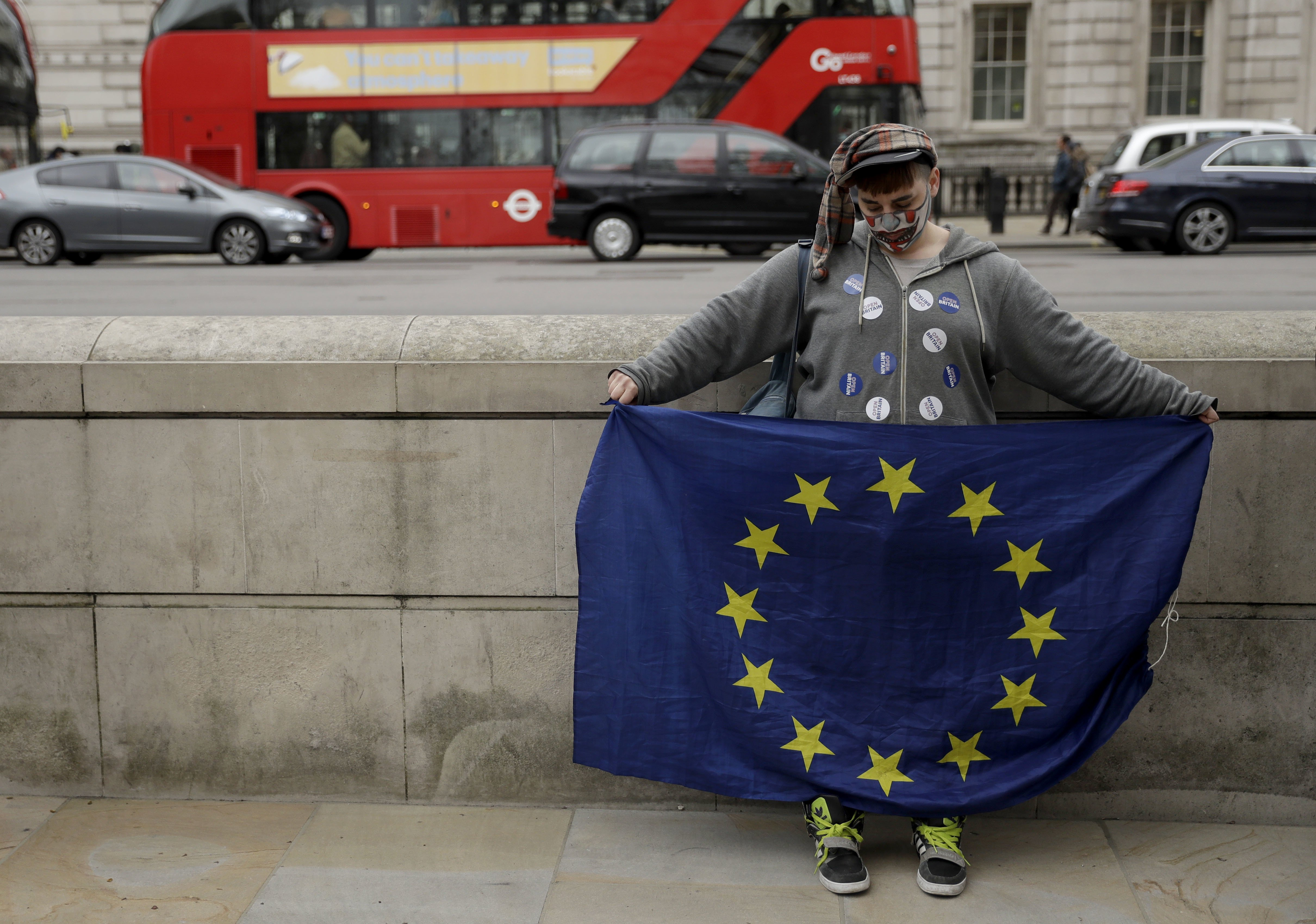 A pro-European Union membership supporter holds a European flag opposite Downing Street in central London, on March 29, 2017.