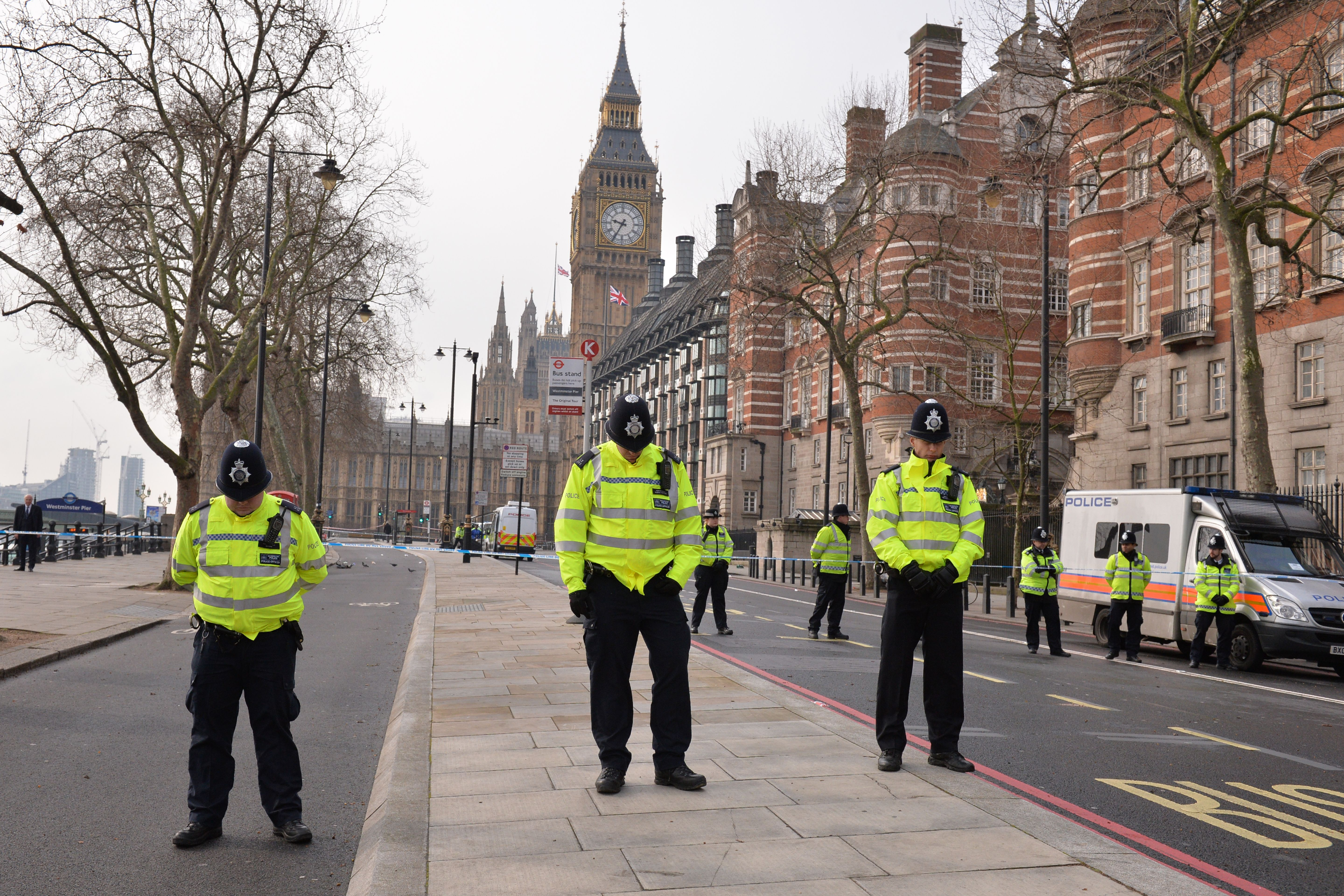 British police officers bow their heads as they stand near a police cordon directly outside New Scotland Yard and within sight of the Houses of Parliament in central London on March 23, 2017.