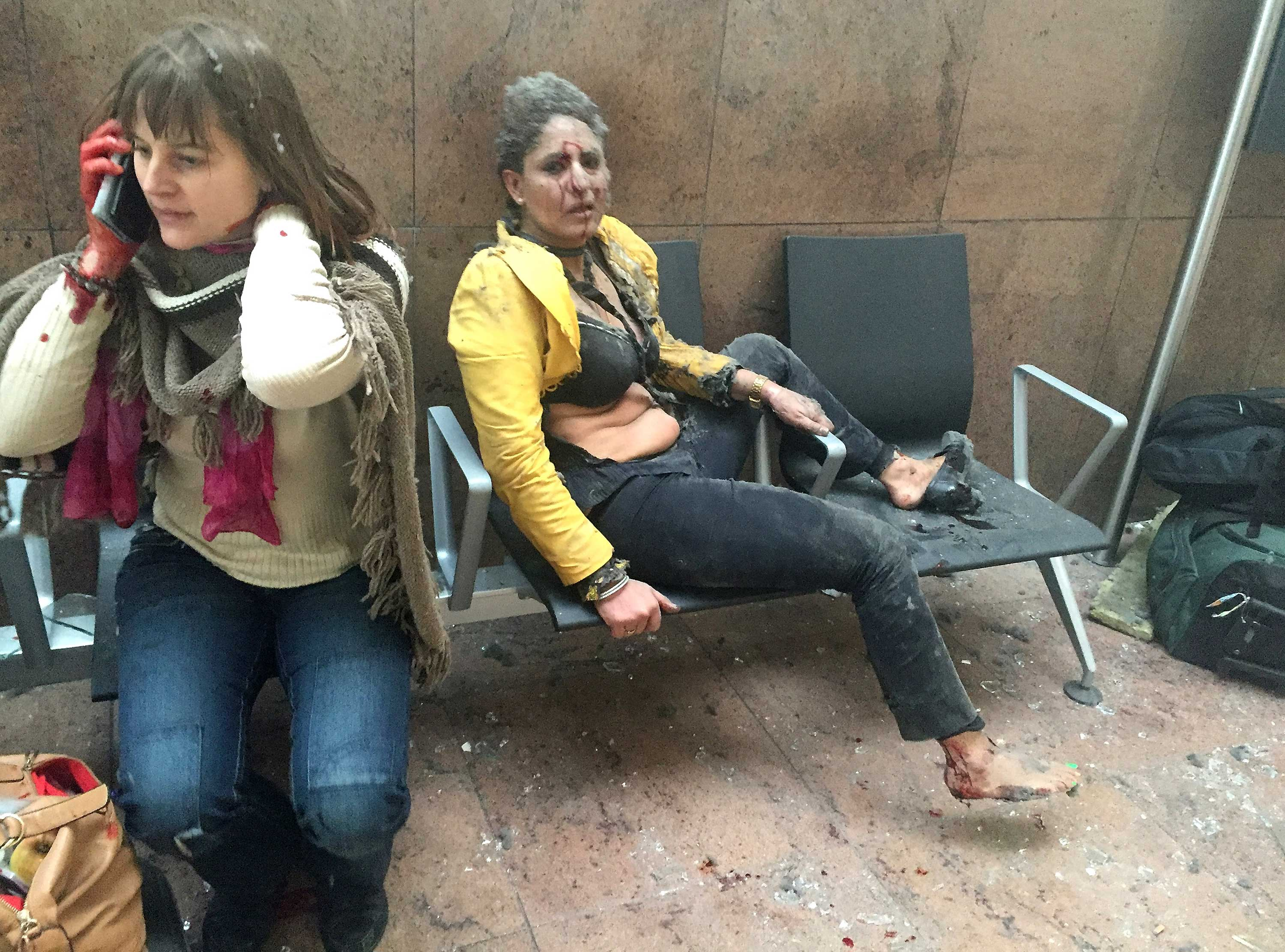 Flight attendant Nidhi Chaphekar (R) reacts in the moments following a suicide bombing at Brussels Zaventem airport on March 22, 2016 in Brussels, Belgium. Georgian journalist Ketevan Kardava, special correspondent for the Georgian Public Broadcaster, was traveling to Geneva when the attack took place; she was knocked to the floor and began to take photographs in the moments that followed.