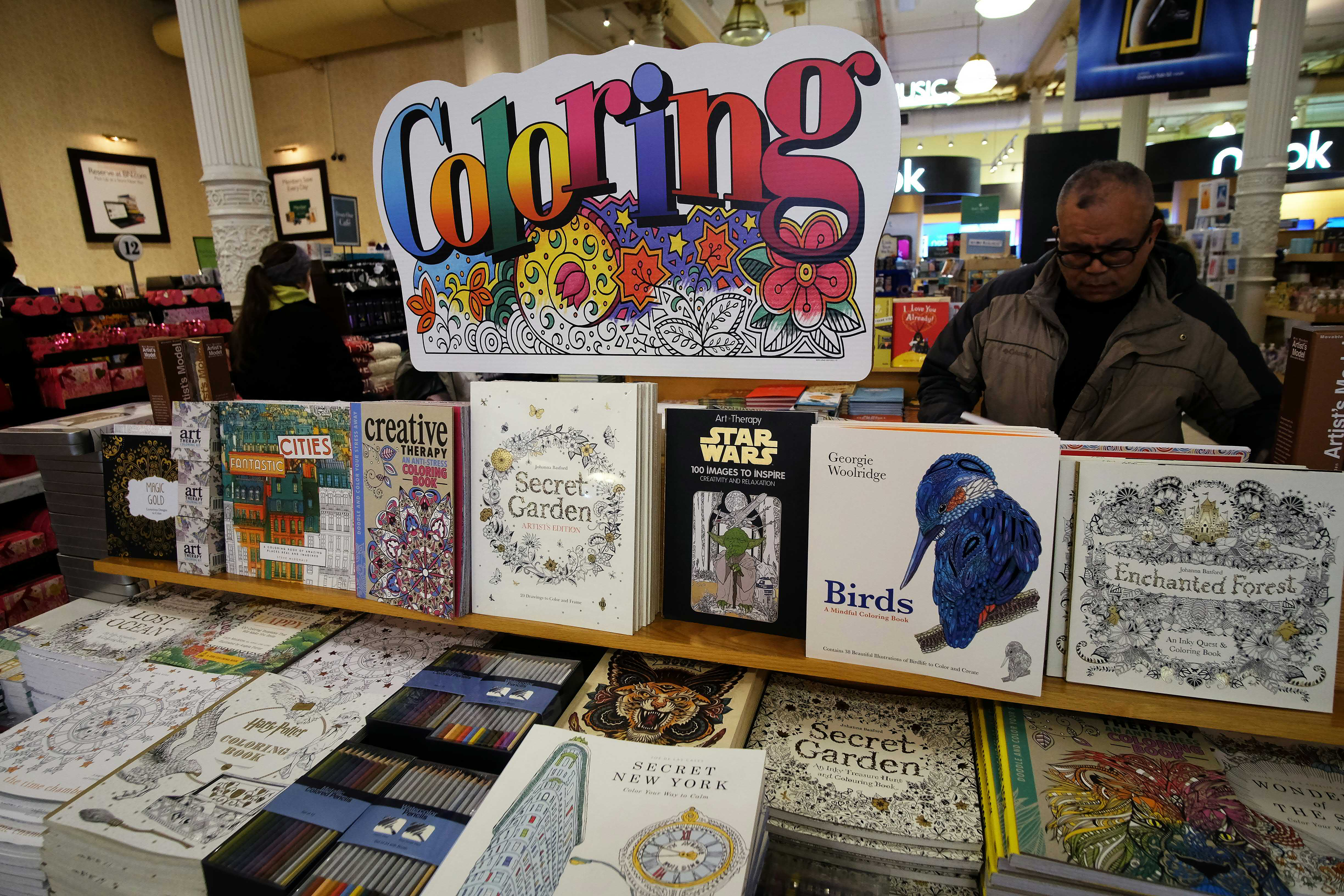A man checks out coloring pencils next to adult coloring books at a Barnes and Nobel store in New York on January 15, 2016.