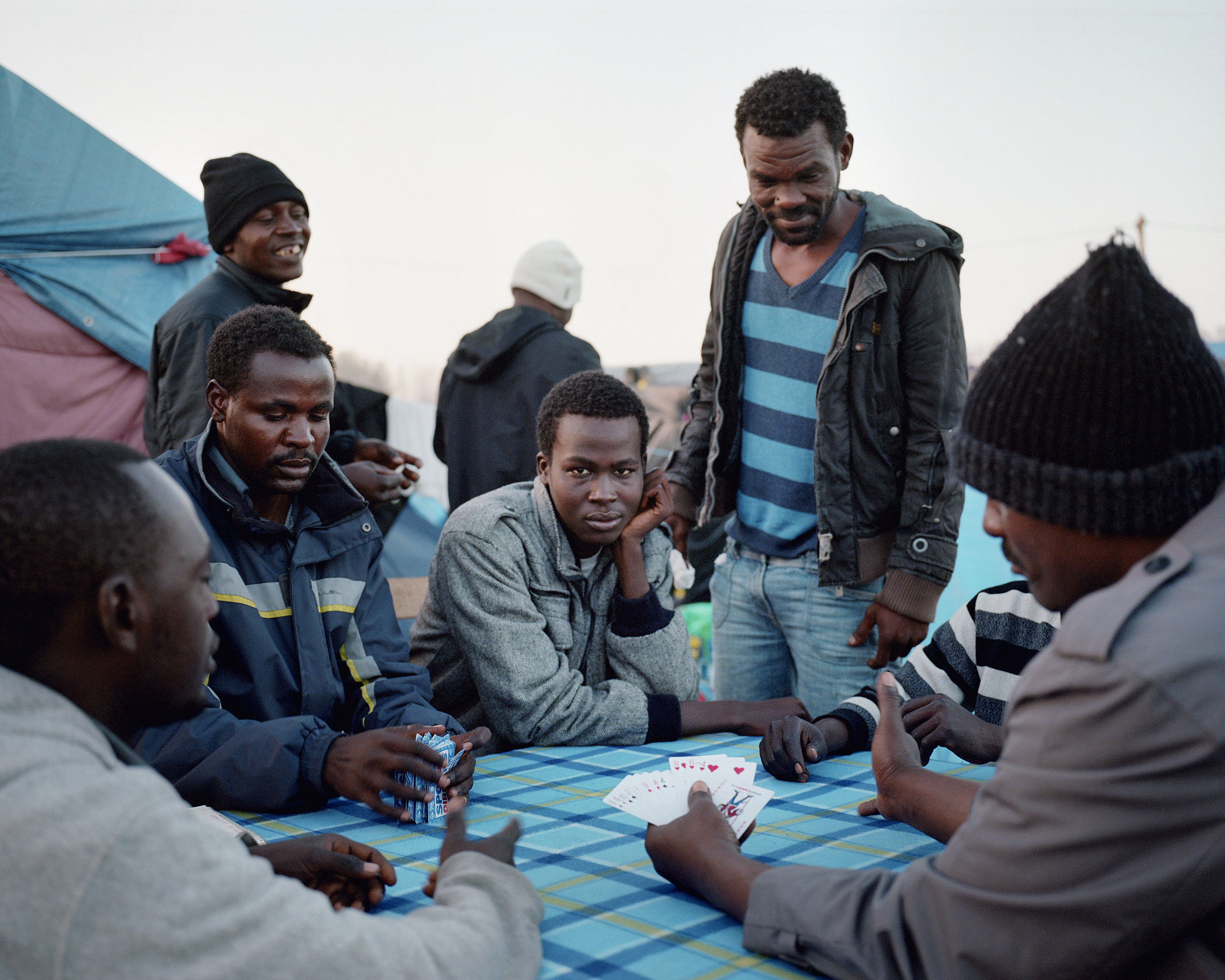 Sudanese men play cards to pass the time in the Calais  Jungle .