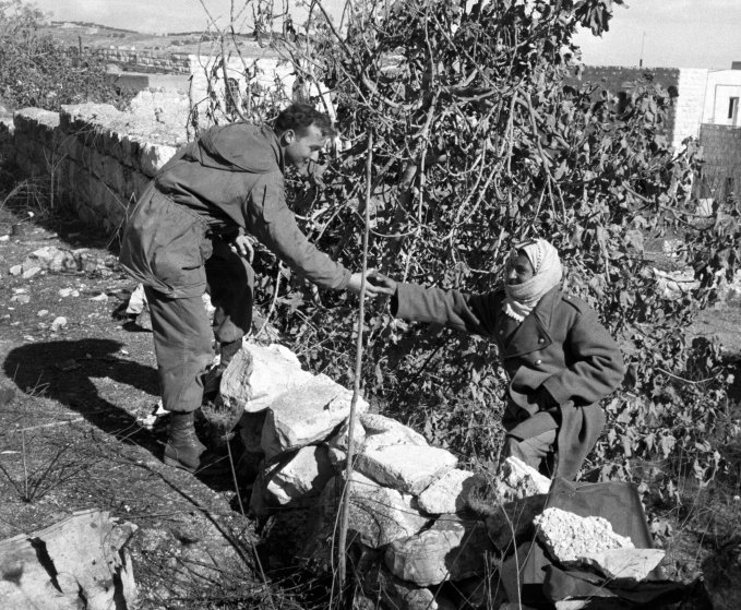 """A Jordanian soldier hands a cup of tea to an Israeli paratrooper, at the dividing """"Green Line"""" in Jerusalem, 1956."""
