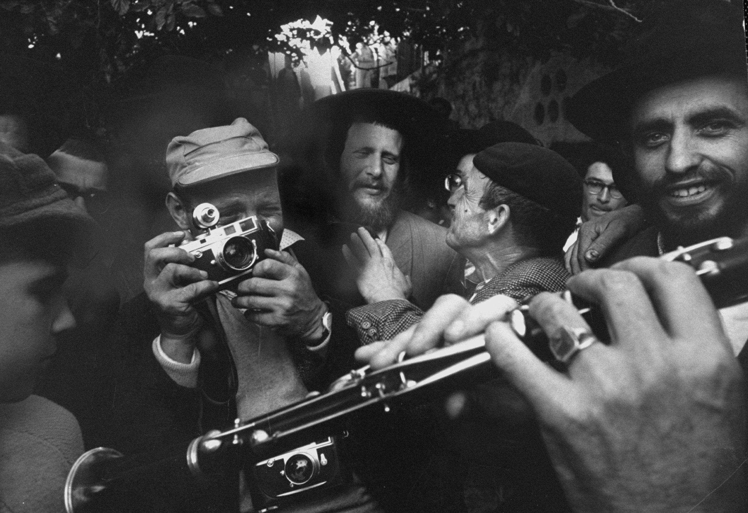 David Rubinger (center L), taking photographs at a religious festival in Israel.