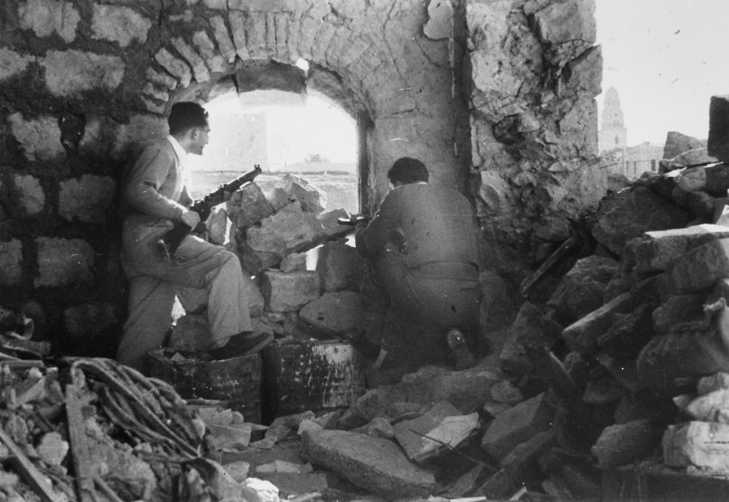 Haganah fighters in action behind barricade of crumbled Old City walls opposite Jordan's Arab Legion, 1948.