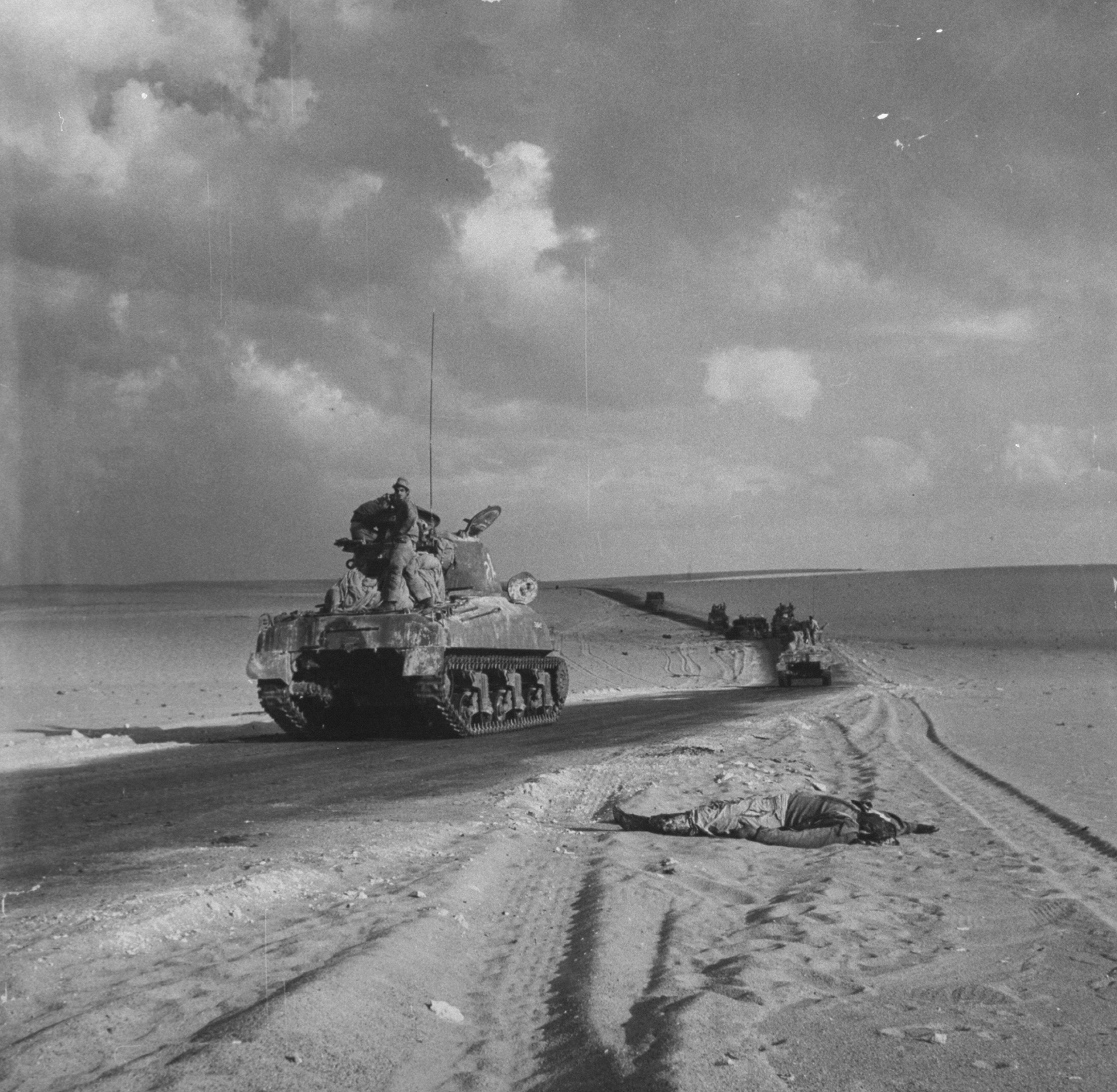 Line of tanks manned by Israelis going through desert, a dead soldier in foreground, 1956.