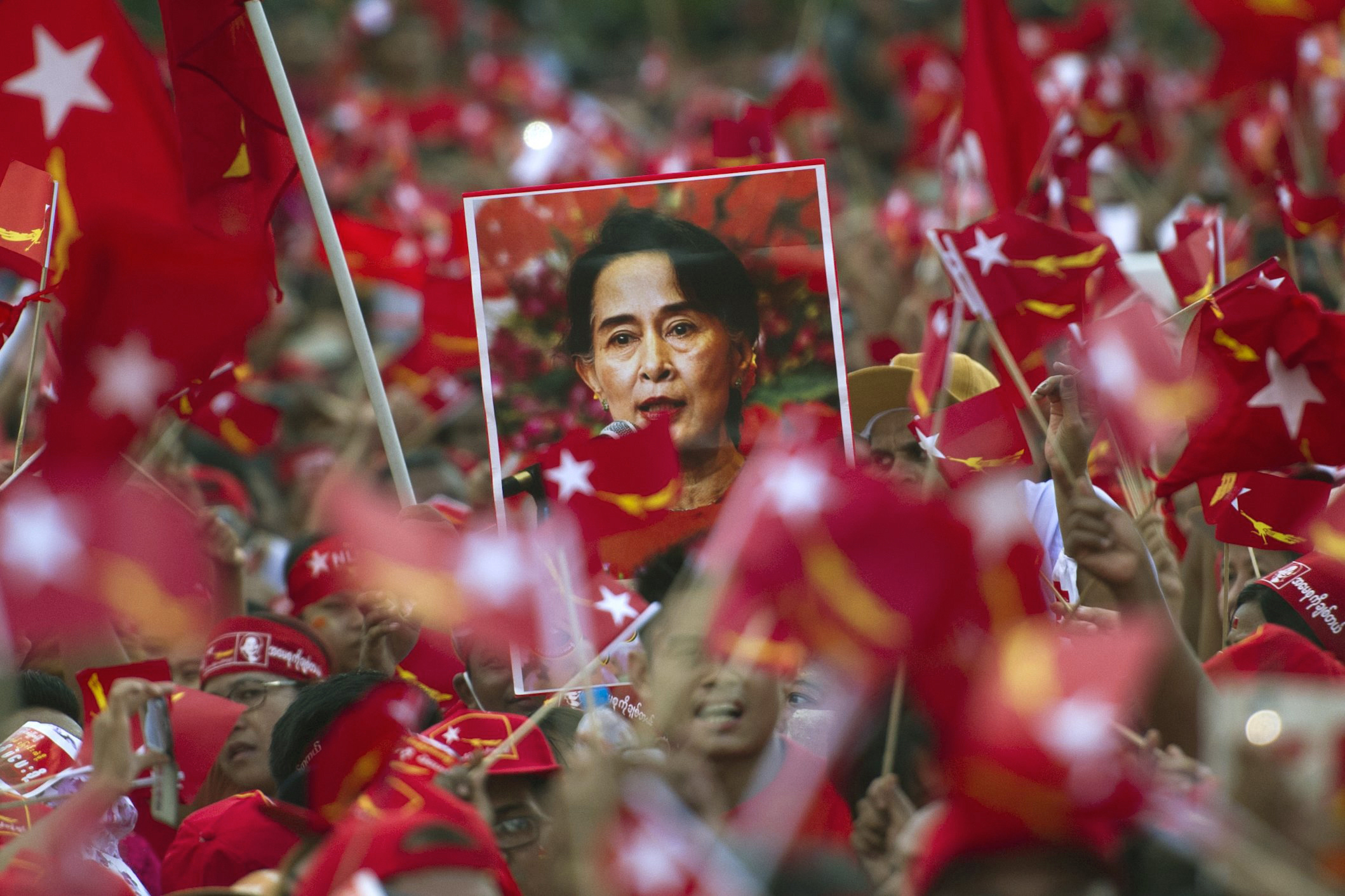 Supporters of opposition leader Aung San Suu Kyi hold posters bearing her image as they listen during a campaign speech in Yangon, Myanmar, on Nov. 1, 2015