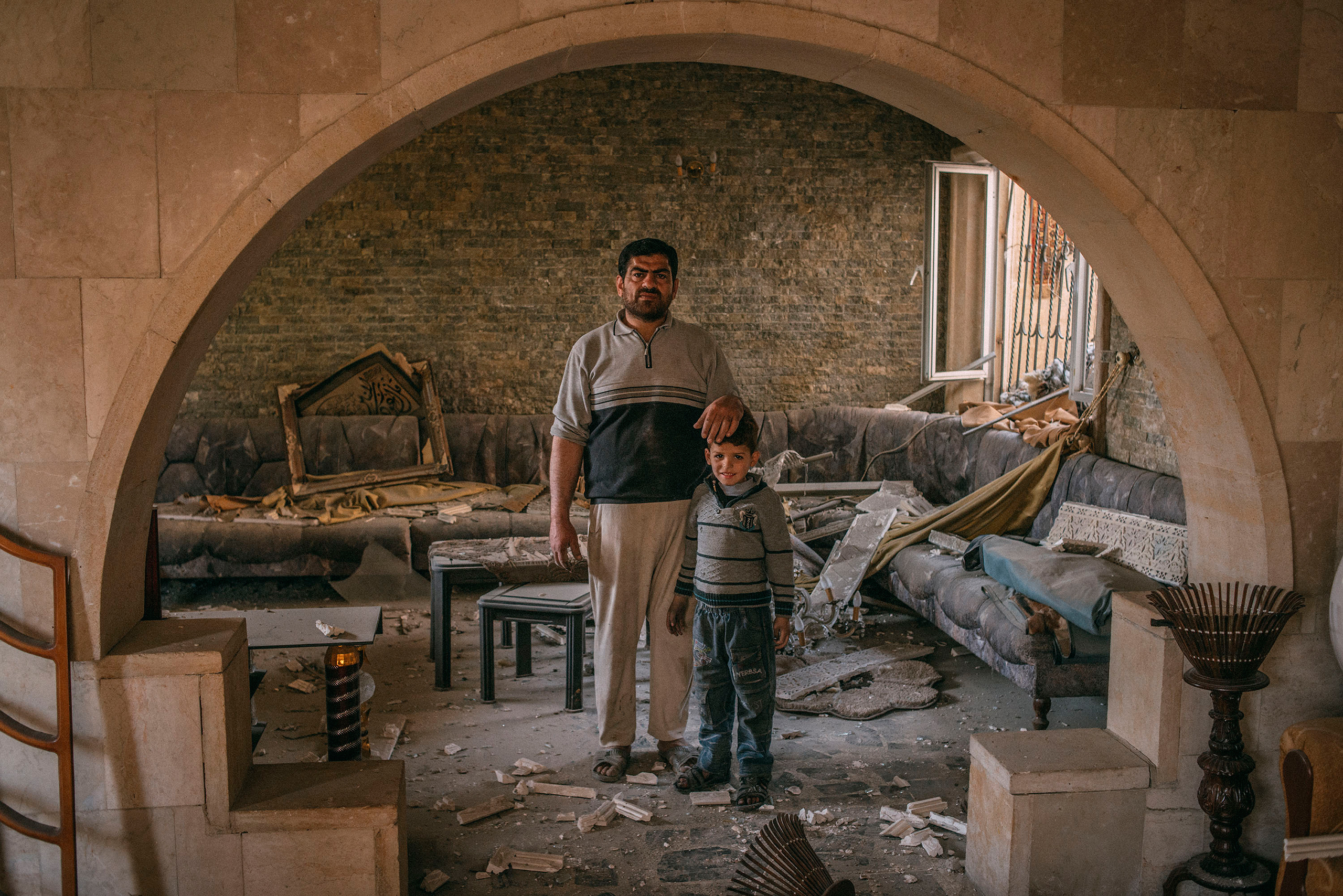 Median Hikmat al-Galou with his son inside their home that was ravaged in February during fighting between Iraqi forces and ISIS in southwest Mosul on March 29, 2017.