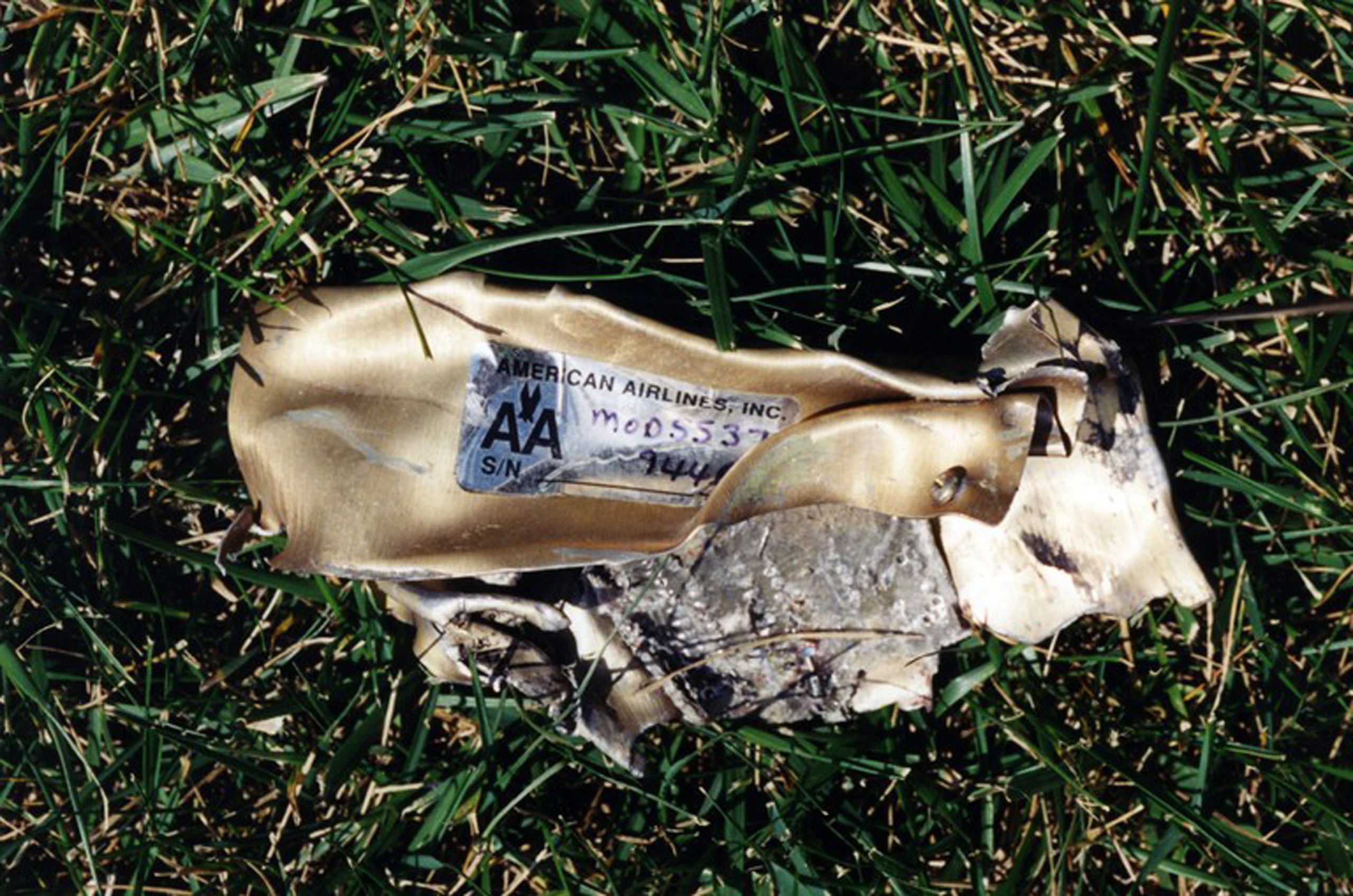 Mangled debris from a plane sits in grass after the hijacked American Airlines Flight 77 crashed into the Pentagon in Arlington County, Virginia, on Sept. 11, 2001.