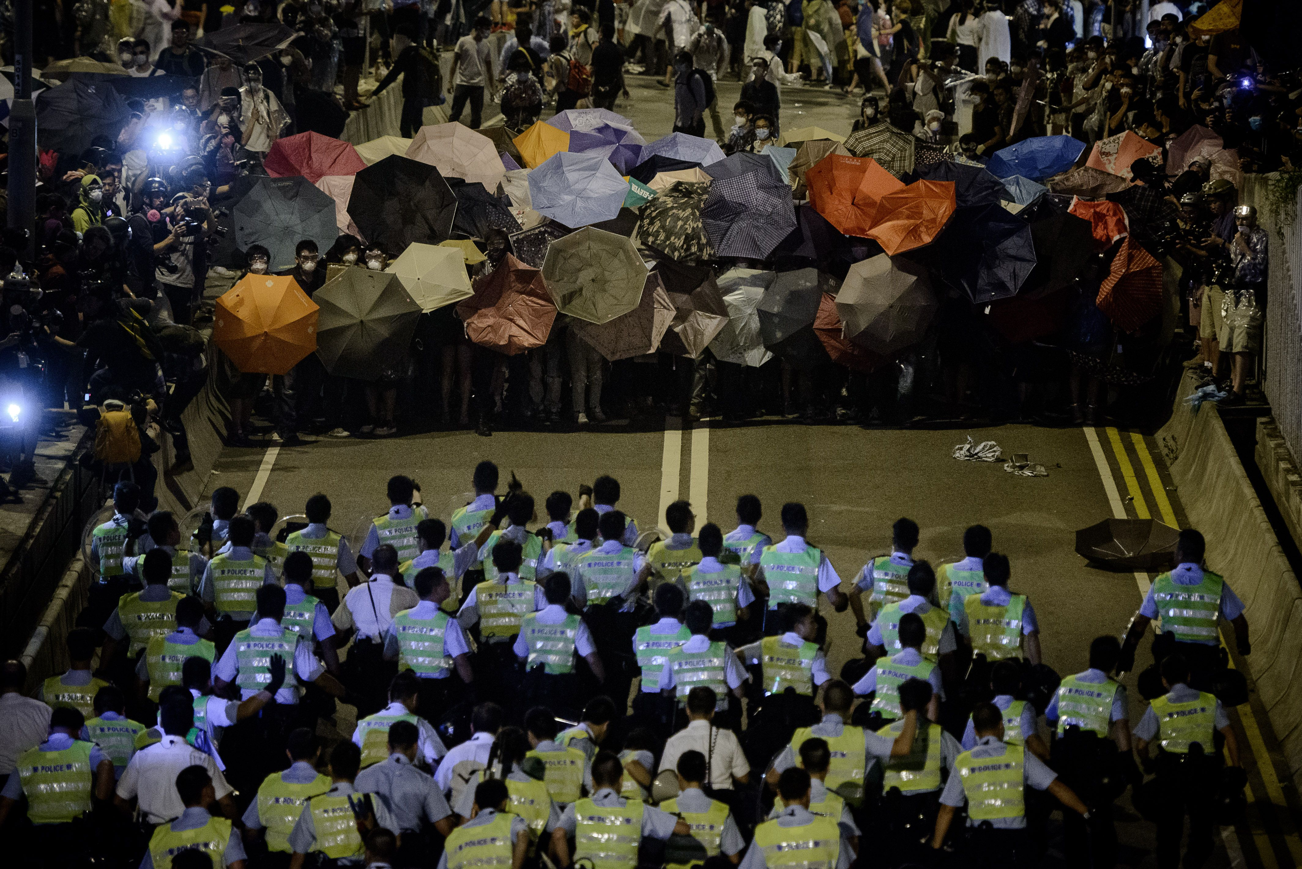 Police forces march toward pro-democracy protesters during a standoff outside the central government offices in Hong Kong on Oct. 14, 2014
