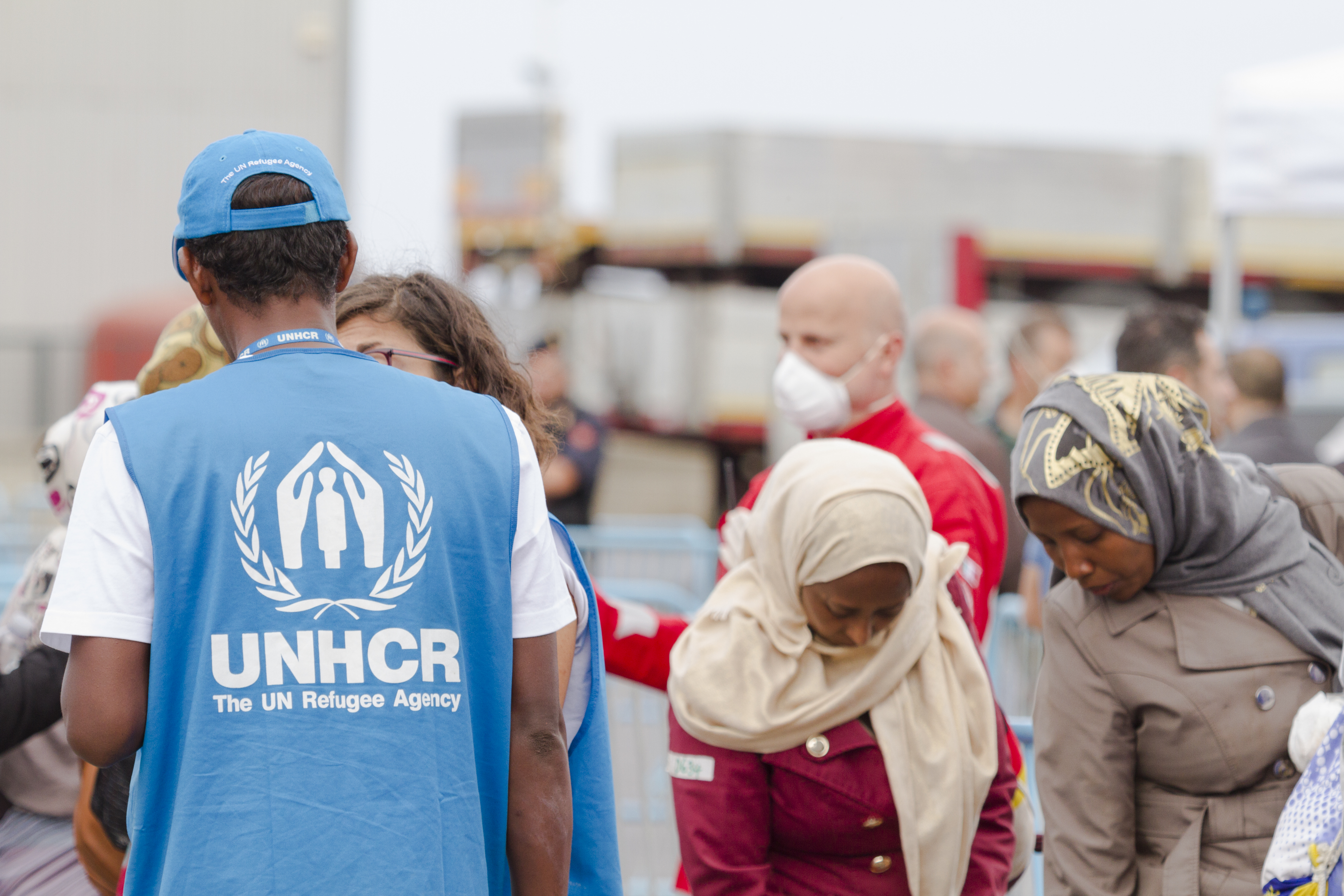 Members of the UNHCR attend to migrants rescued at sea by the Royal Navy warship HMS Bulwark, on June 08, 2015 in Catania, Italy.