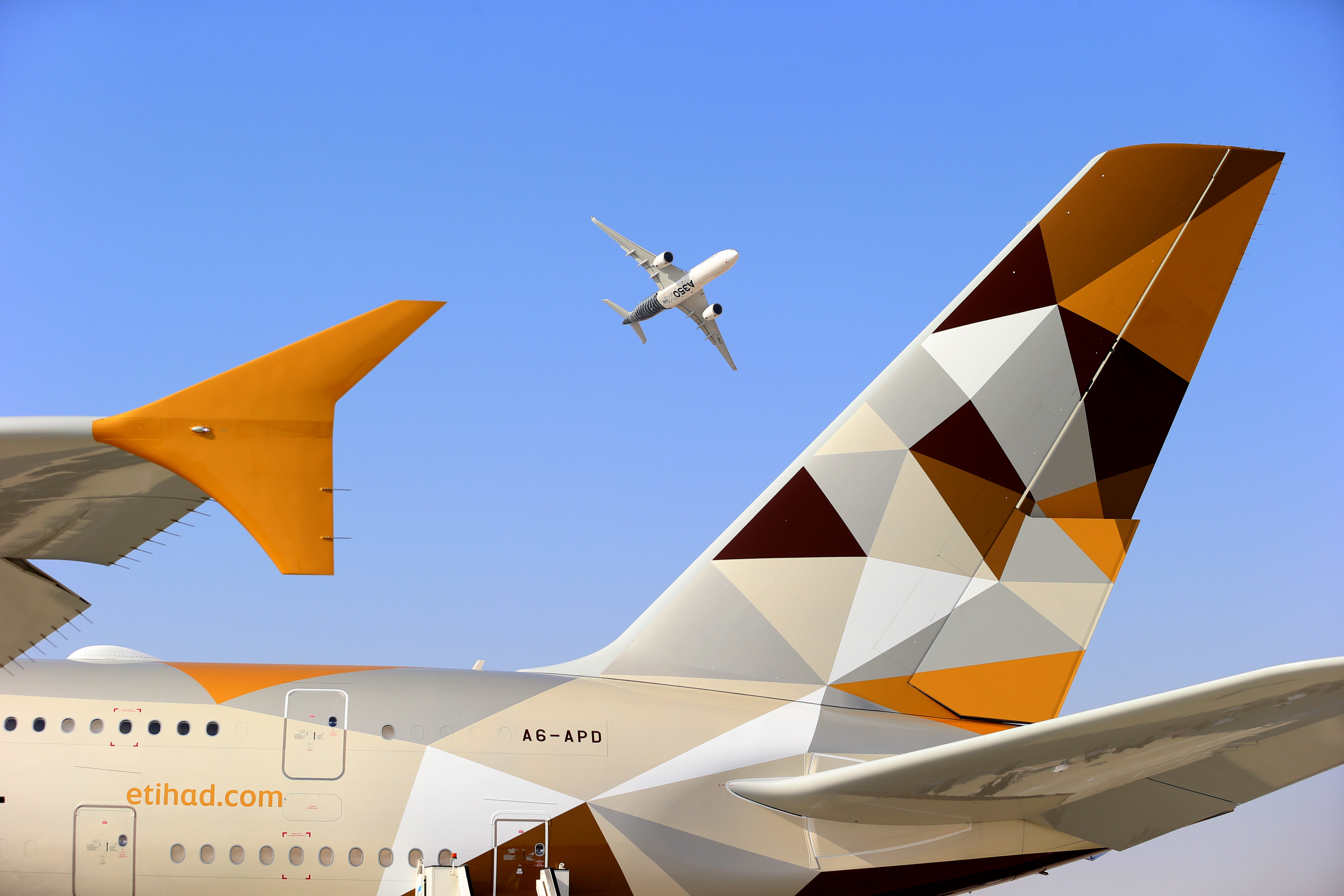 An Airbus A350-900 aircraft, manufactured by Airbus SAS, performs an aerial display above the tail fin of an Airbus A380 aircraft, operated by Eithad Airways, on the second day of the 14th Dubai Air Show at Dubai World Central (DWC) in Dubai, United Arab Emirates, on Monday, Nov. 9, 2015. The Dubai Air Show is the biggest aerospace event in the Middle East, Asia and Africa and runs Nov. 8 - 12. Photographer: Jasper Juinen/Bloomberg via Getty Images