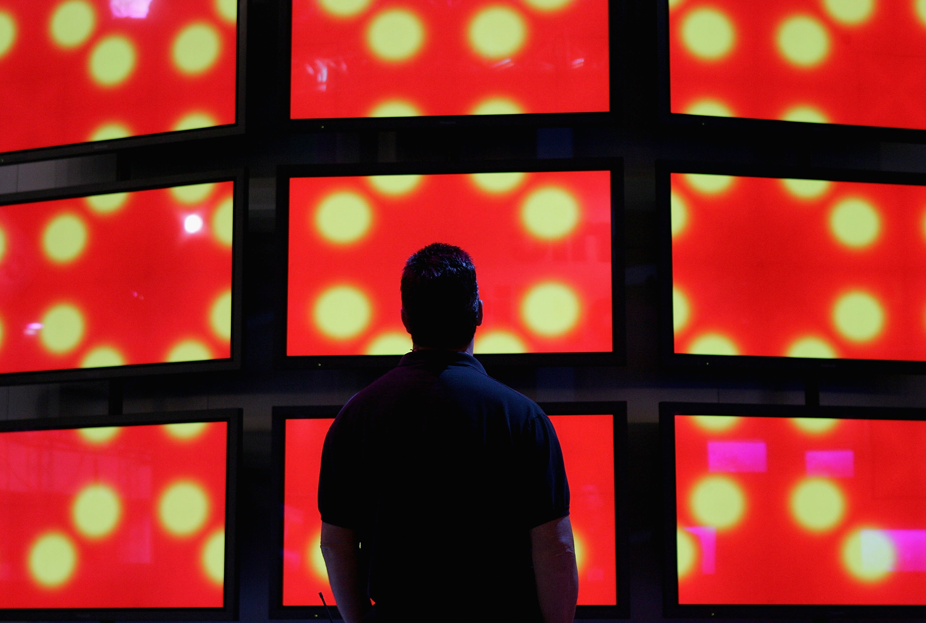 A man looks at a wall of Panasonic high definition televisions on display at the 2005 Consumer Electronics Show in Las Vegas, Nevada on Jan. 5, 2005.