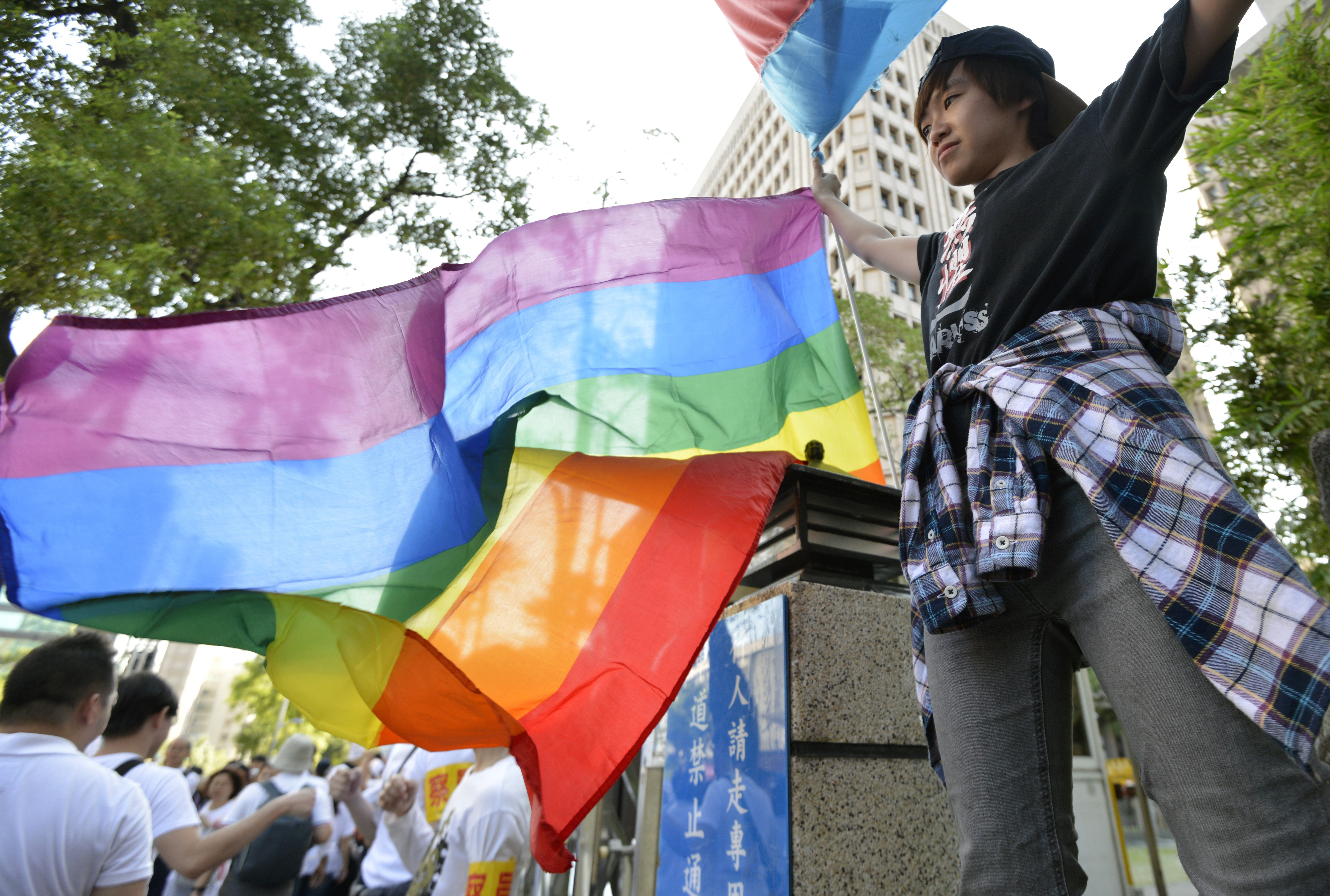 A same-sex marriage supporter displays a rainbow flag outside the parliament in Taipei on Nov.17, 2016