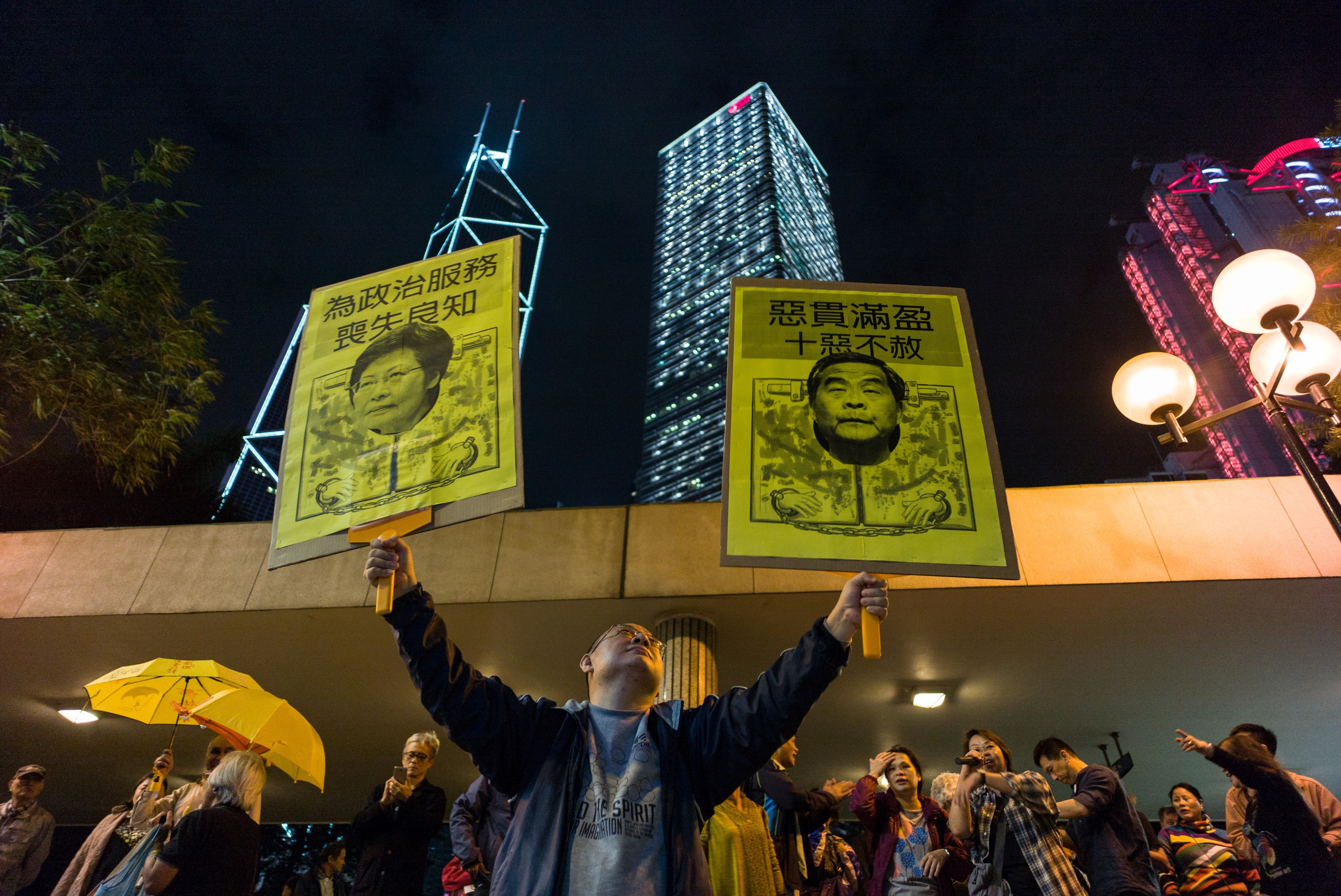 A pro-democracy protester holds up placards featuring Hong Kong's former Chief Secretary Carrie Lam and Chief Executive Leung Chun-ying during a rally in Hong Kong on Dec. 11, 2016