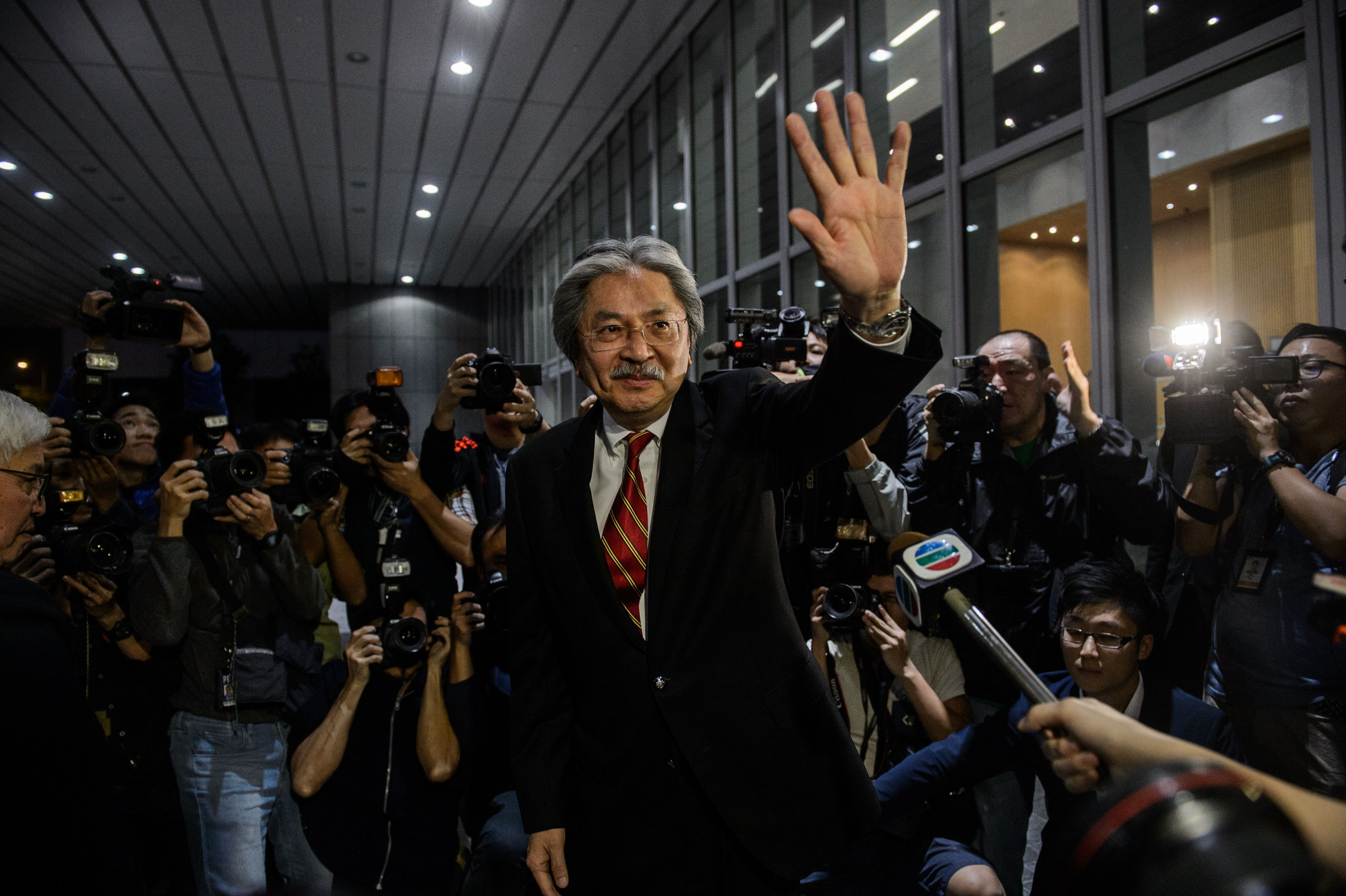 Hong Kong's former Financial Secretary John Tsang waves as he leaves a press conference to announce his resignation in Hong Kong on Dec. 12, 2016
