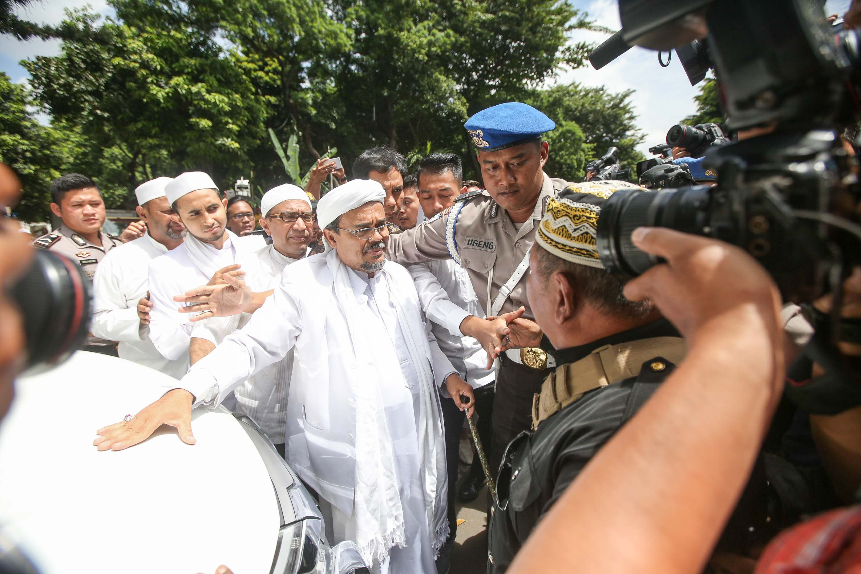 Leader of the Islamic Defenders Front (FPI), Habib Rizieq Shihab, is escorted by police at police headquarters for questioning, on Jan. 23, 2017, in Jakarta