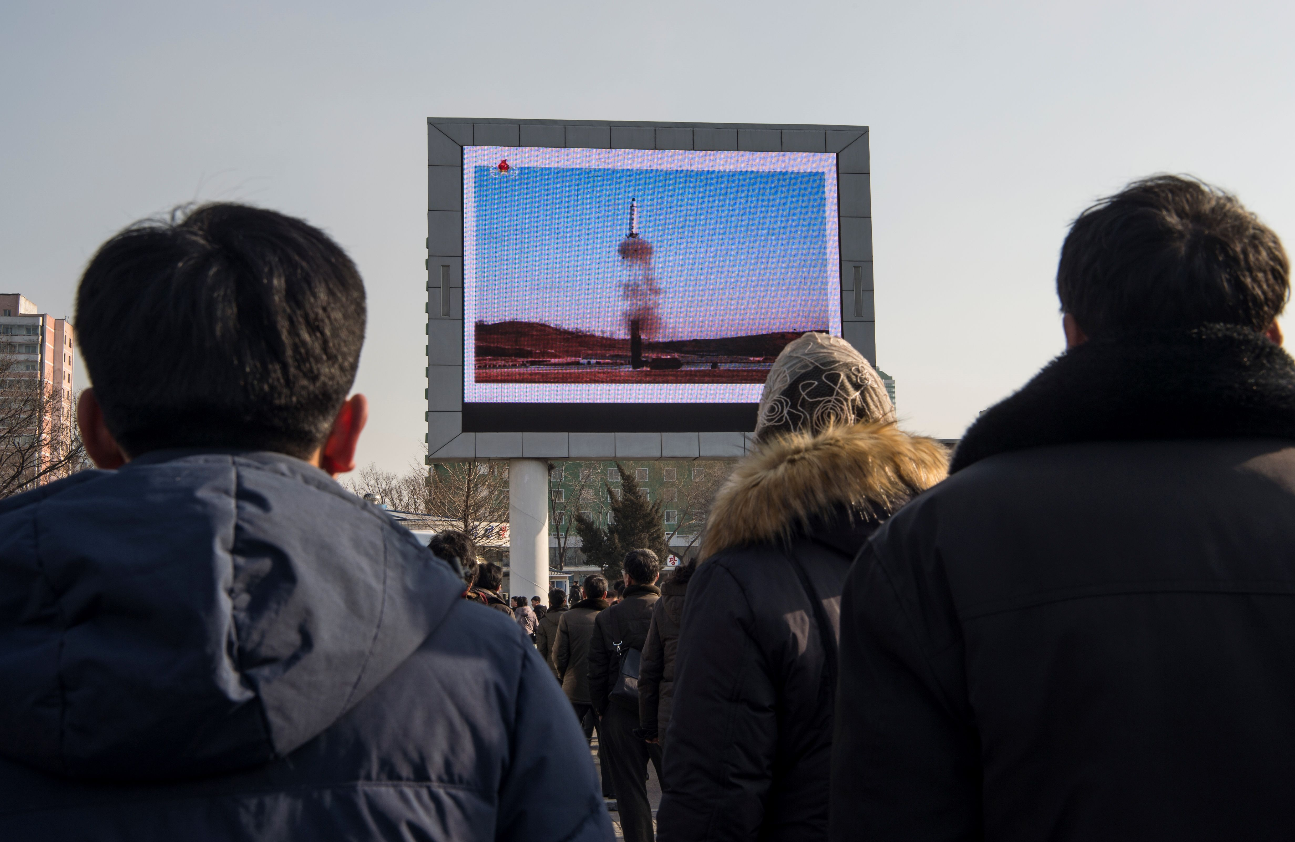 This photo taken on Feb. 13, 2017 shows people in Pyongyang watching a public broadcast about the launch of a medium long-range ballistic missile.