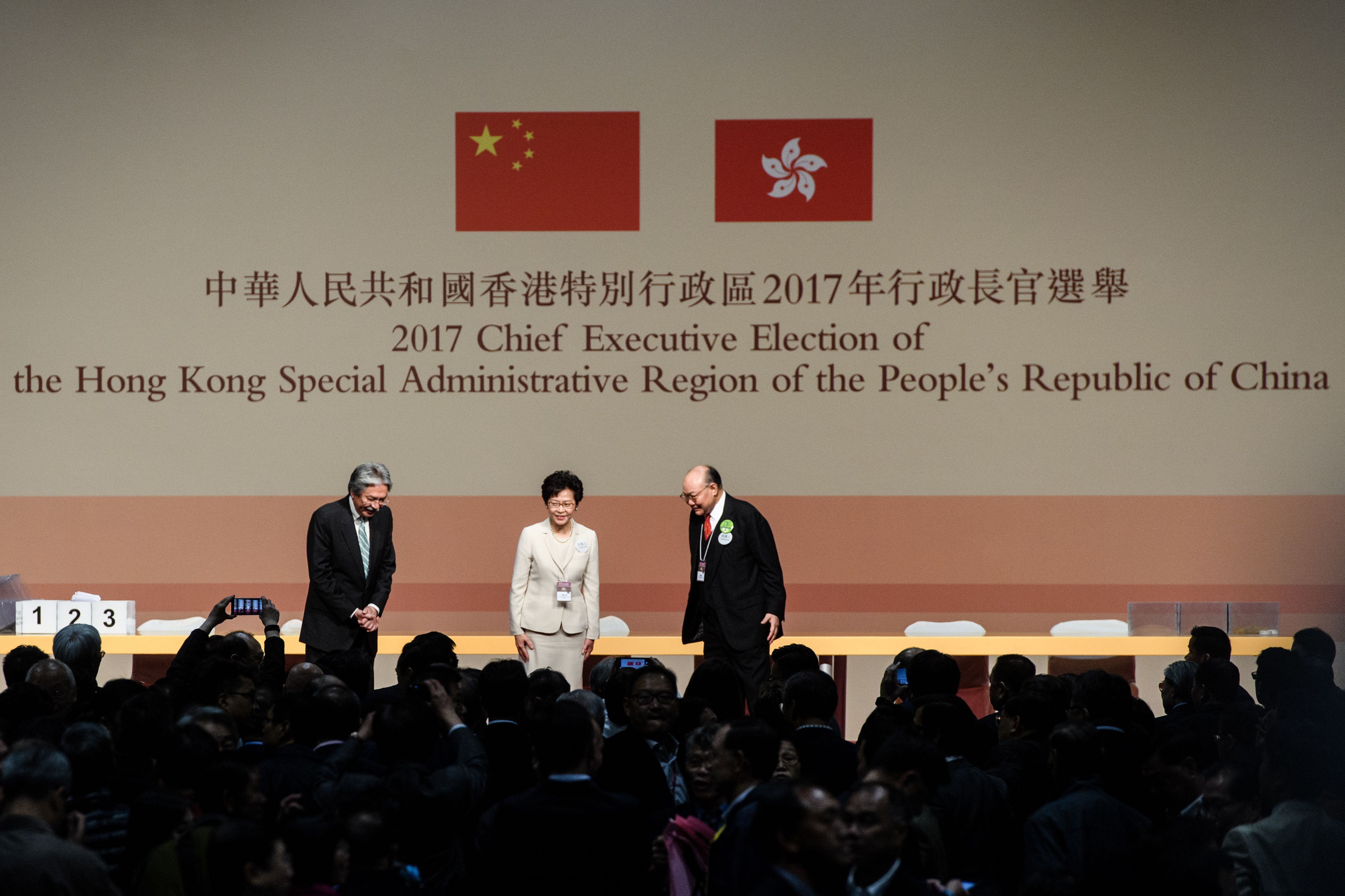 Hong Kong's new Chief Executive Carrie Lam, center, stands on stage with her defeated opponents John Tsang, left, and Woo Kwok-hing, right, in Hong Kong on March 26, 2017