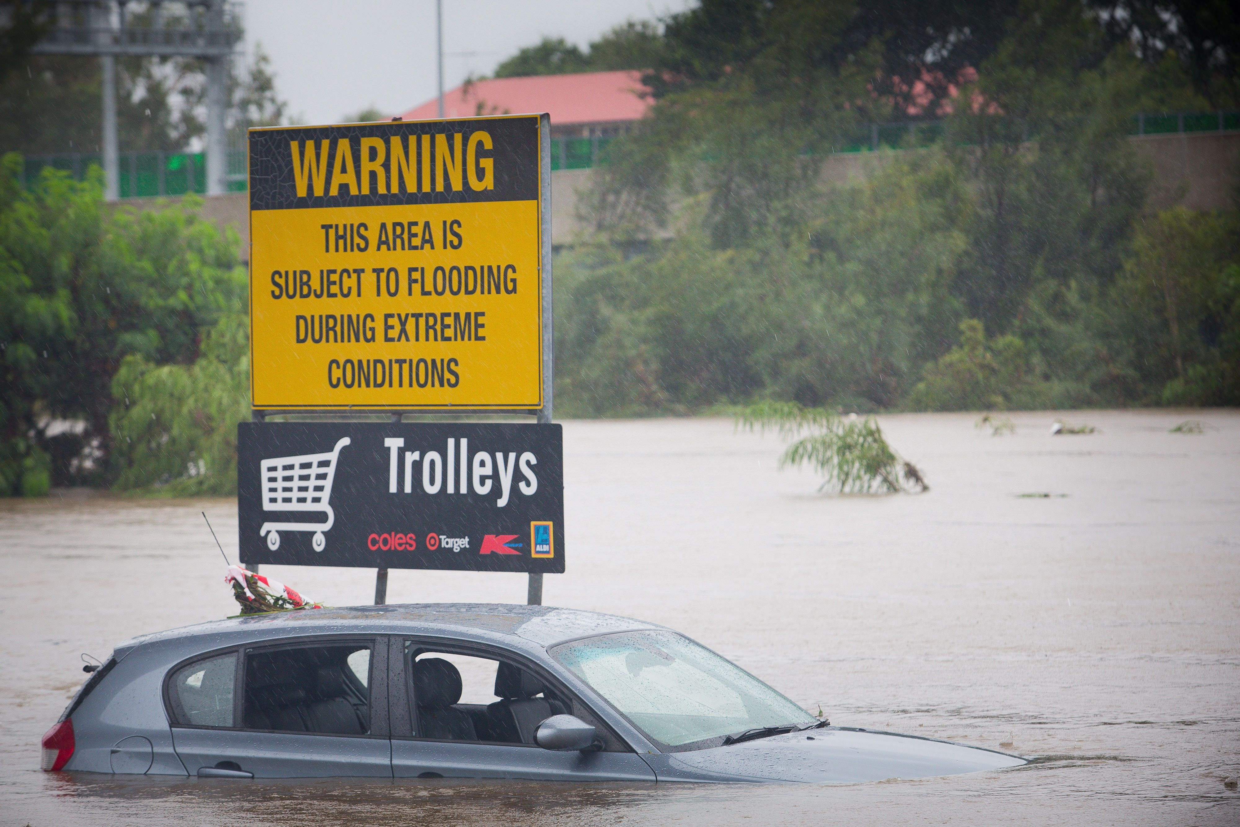 Submerged cars sit in a flooded carpark in Toombul, in Australia's state of Queensland, on March 30, 2017