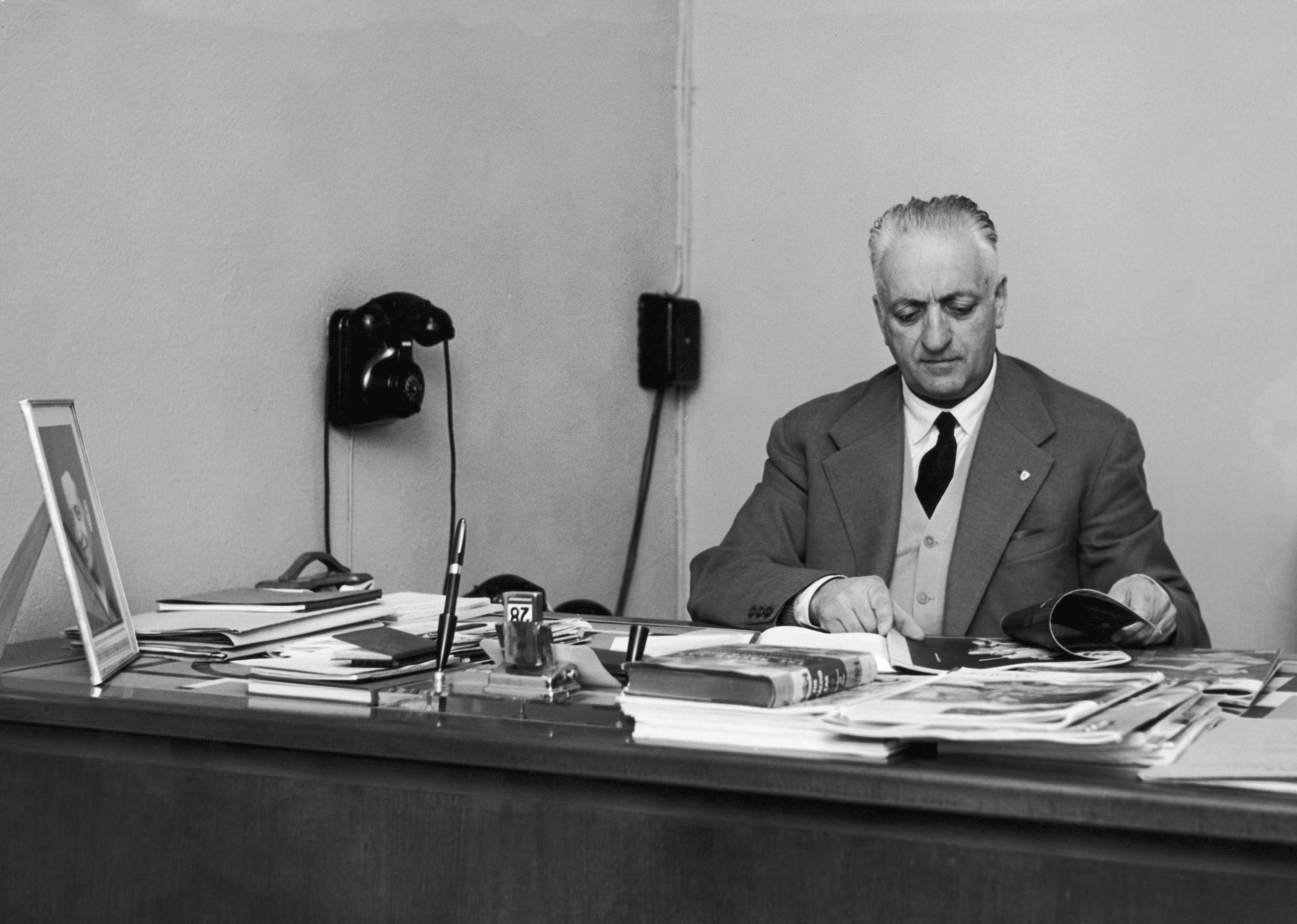 Italian car manufacturer Enzo Ferrari (1898 - 1988) at his desk, circa 1955.