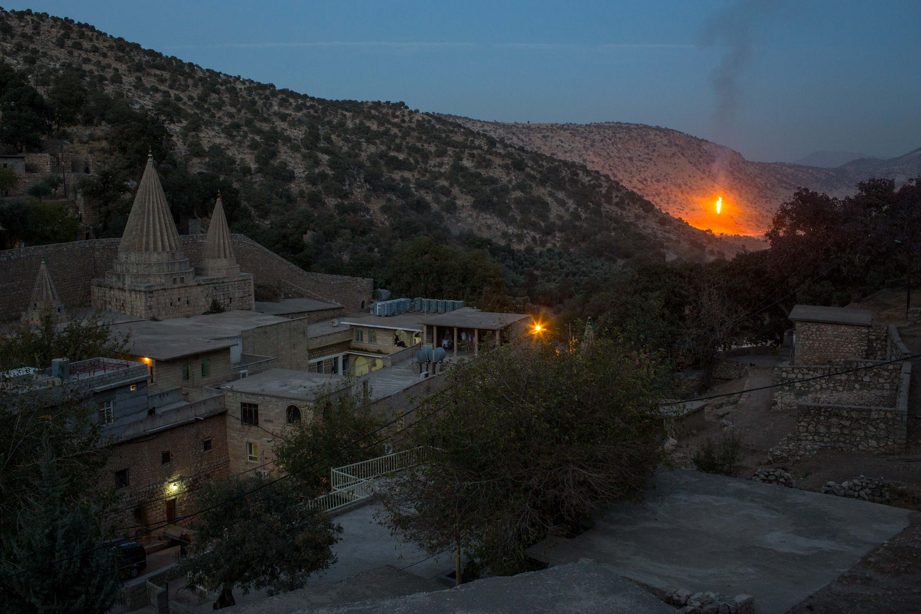 An oil refinery is seen behind the holiest temple of the Yazidi faith after Friday rituals on Nov. 11, 2016 in Lalish, Iraq. In 2014, thousands of Yazidis fled to the villages of Lalish and Shekhan after ISIS took control of Sinjar and other Yazidi populated towns. Many Yazidi resettled in Mosul and Bashiqah but were forced to flee again when ISIS took control of the cities.